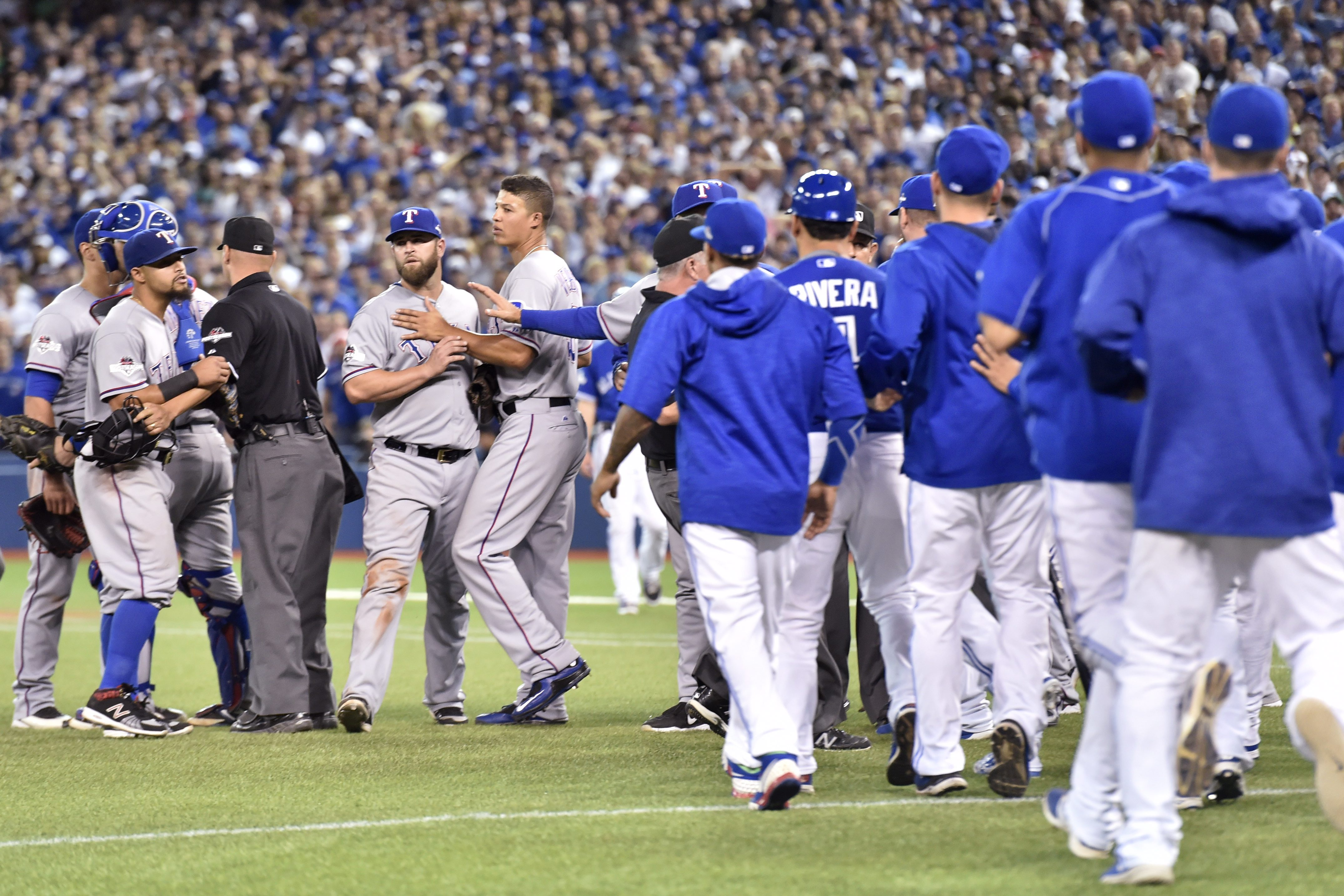 Players on both sides are restrained following an exchange of words between Toronto Blue Jays' Josh Donaldson and Texas Rangers' Keone Kela during the 13th inning of baseball Game 2 of the American League Division Series in Toronto, Friday, Oct. 9, 2015.