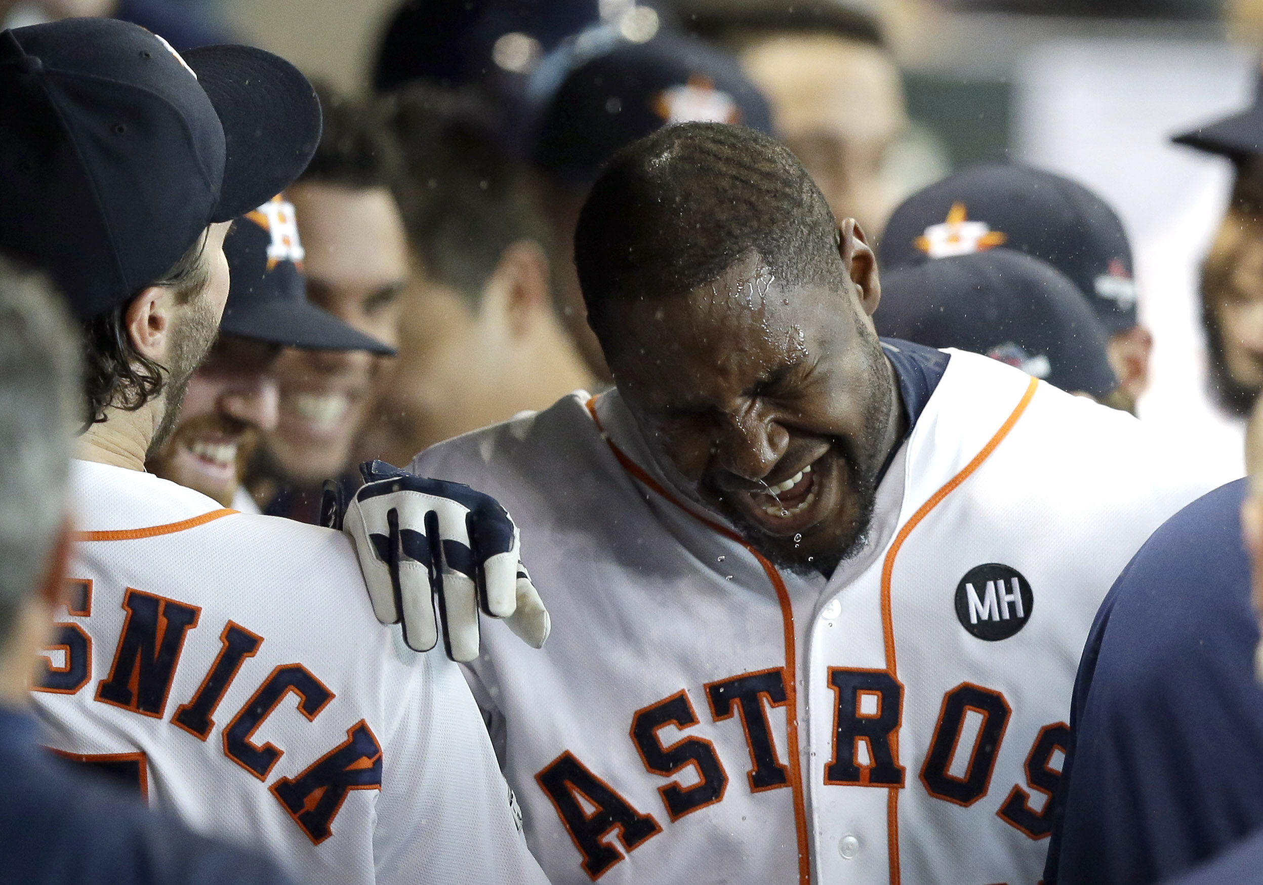 Houston Astros' Chris Carter is splashed with water in the dugout after hitting a home run against the Kansas City Royals during the seventh inning in Game 3 of baseball's American League Division Series Sunday, Oct. 11, 2015, in Houston. (AP Photo/Pat Su