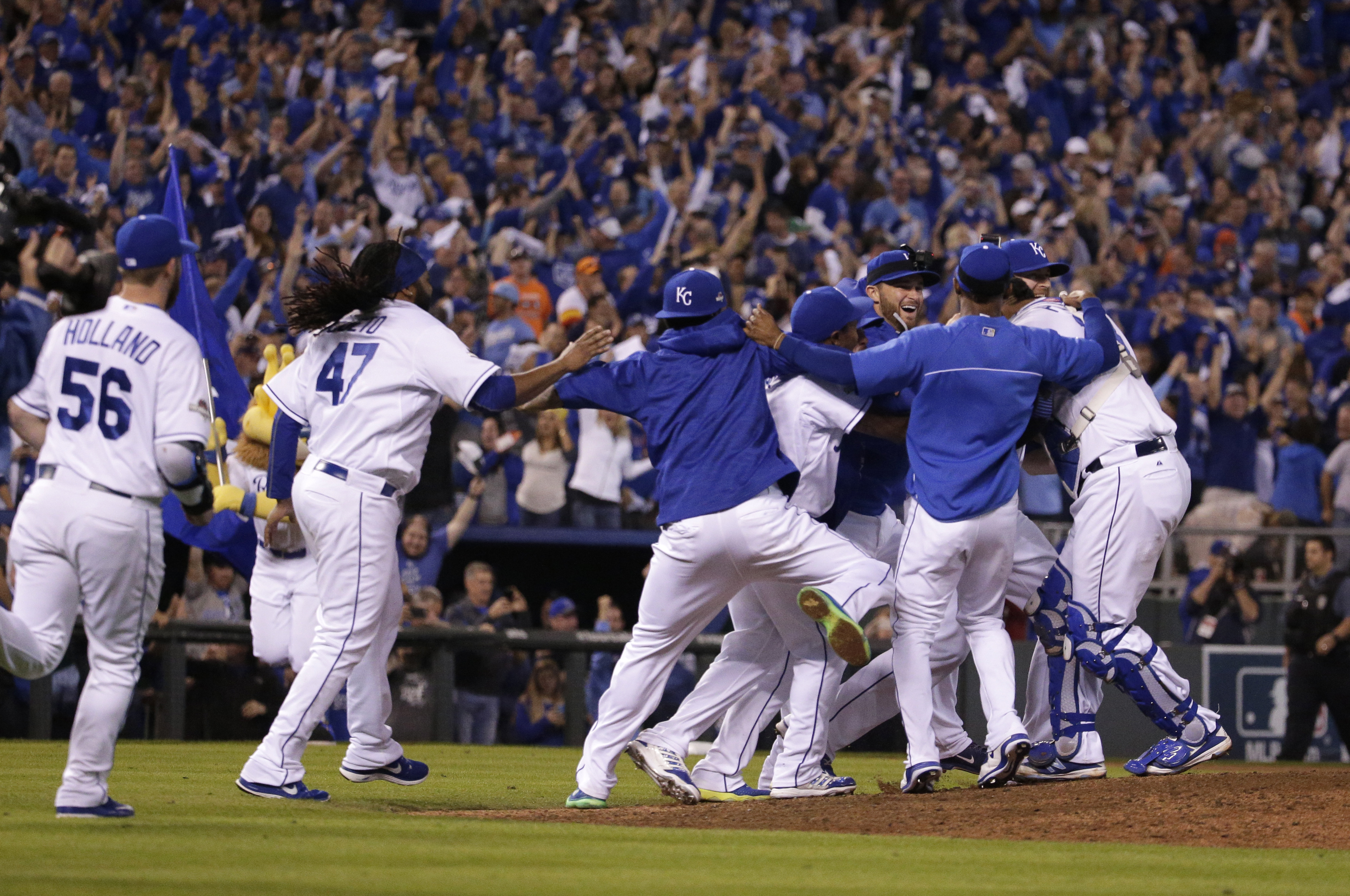 Kansas City Royals players celebrate on the field after their 7-2 win over the Houston Astros in Game 5 of baseball's American League Division Series, Wednesday, Oct. 14, 2015, in Kansas City, Mo. (AP Photo/Charlie Riedel)