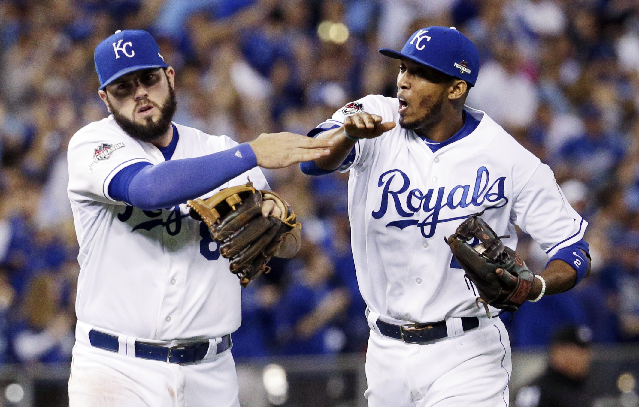 Kansas City Royals third baseman Mike Moustakas, let, and shortstop Alcides Escobar celebrates the end of the top of the fifth inning in Game 6 of baseball's American League Championship Series against the Toronto Blue Jays on Friday, Oct. 23, 2015, in Ka