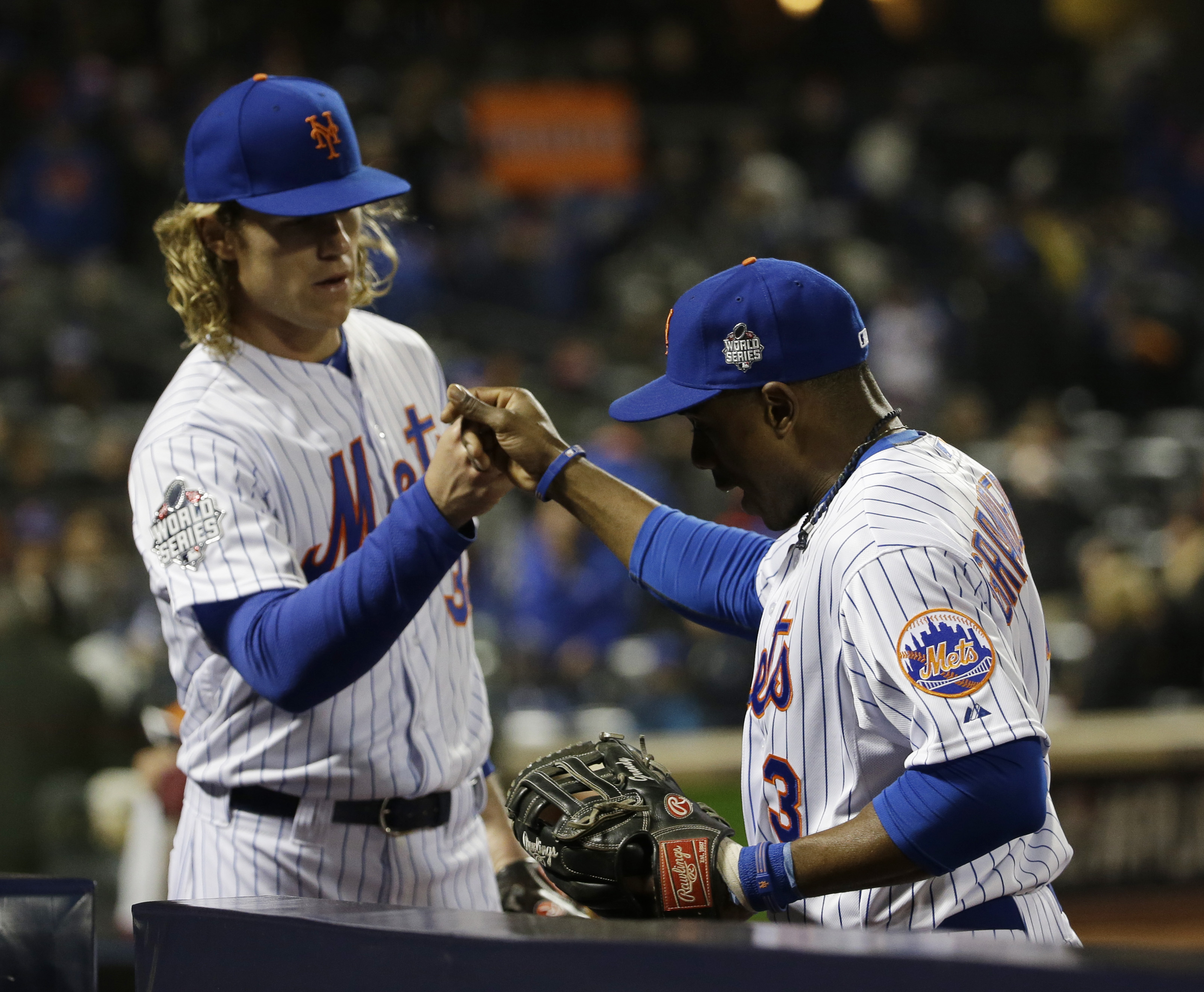 New York Mets pitcher Noah Syndergaard congratulates teammate Curtis Granderson after a catch during the fifth inning of Game 3 of the Major League Baseball World Series against the Kansas City Royals Friday, Oct. 30, 2015, in New York. (AP Photo/David J.