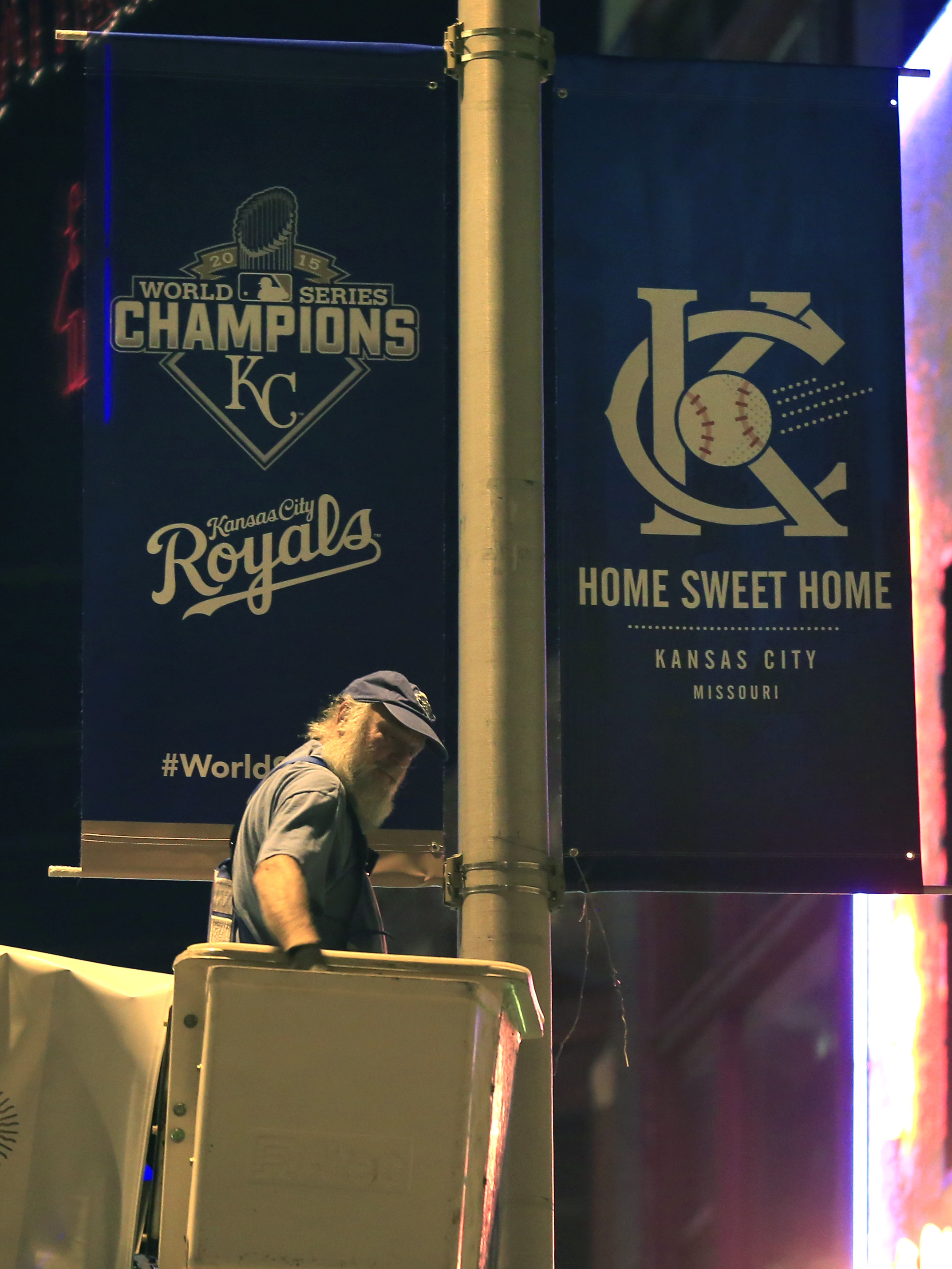 A city worker hangs World Series banners on street light poles in Kansas City, Mo., Monday, Nov. 2, 2015. The Kansas City Royals defeated the New York Mets to win the World Series. (AP Photo/Orlin Wagner)