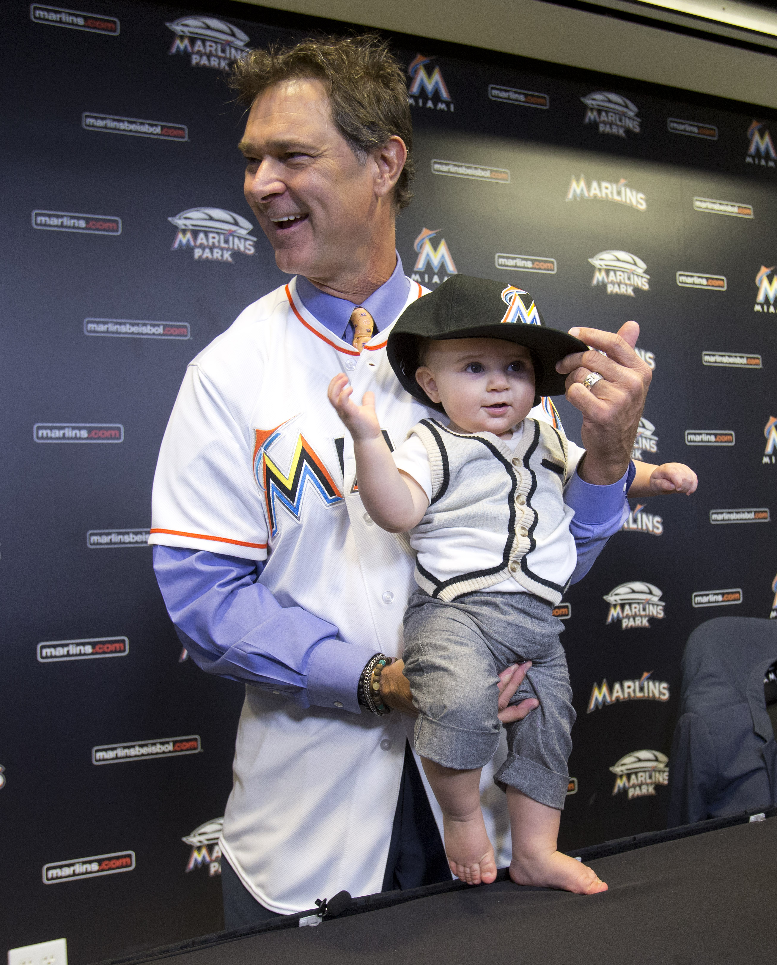 Don Mattingly puts a Miami Marlins baseball hat on his son Louie after being introduced as the new Marlins manager, Monday, Nov. 2, 2015, in Miami. (AP Photo/Wilfredo Lee)
