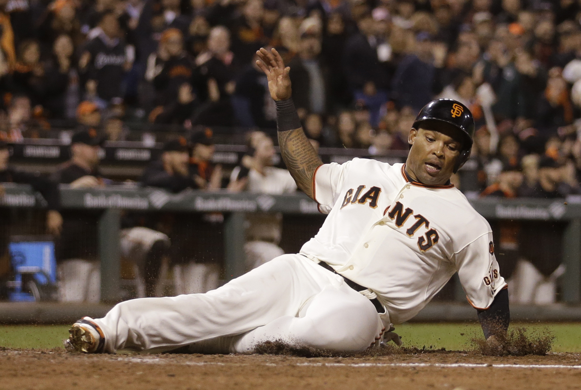 FILE - In this Tuesday, Sept. 15, 2015 file photo, San Francisco Giants' Marlon Byrd slides to score against the Cincinnati Reds in the sixth inning of a baseball game in San Francisco. The Giants declined their 2016 contract options on outfielders Byrd a