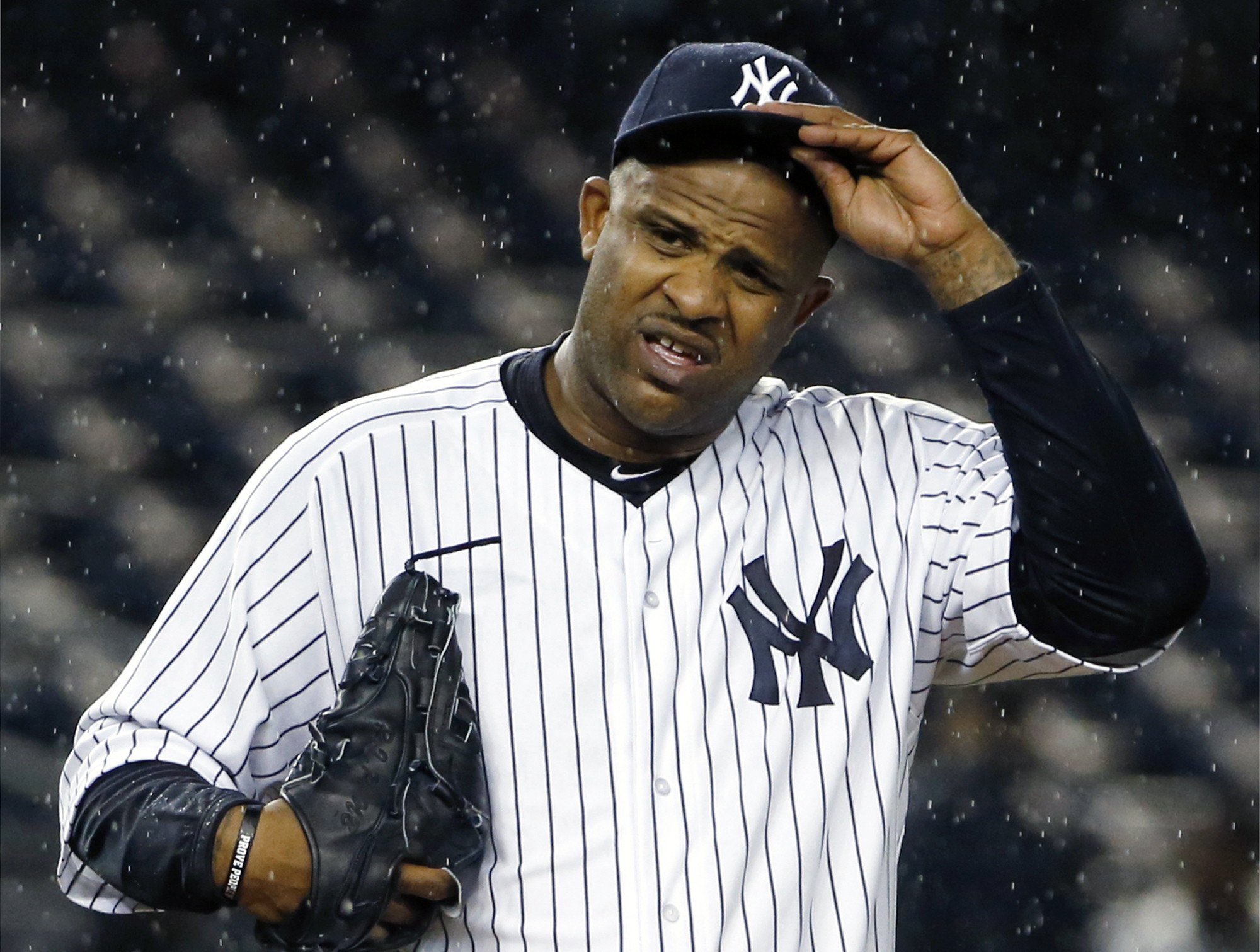 """FILE - In this Oct. 1, 2015, file photo, New York Yankees starting pitcher CC Sabathia (52) struggles with his cap in the rain during the first inning of a baseball game against the Boston Red Sox in New York. Sabathia says he had """"no other option"""" than t"""