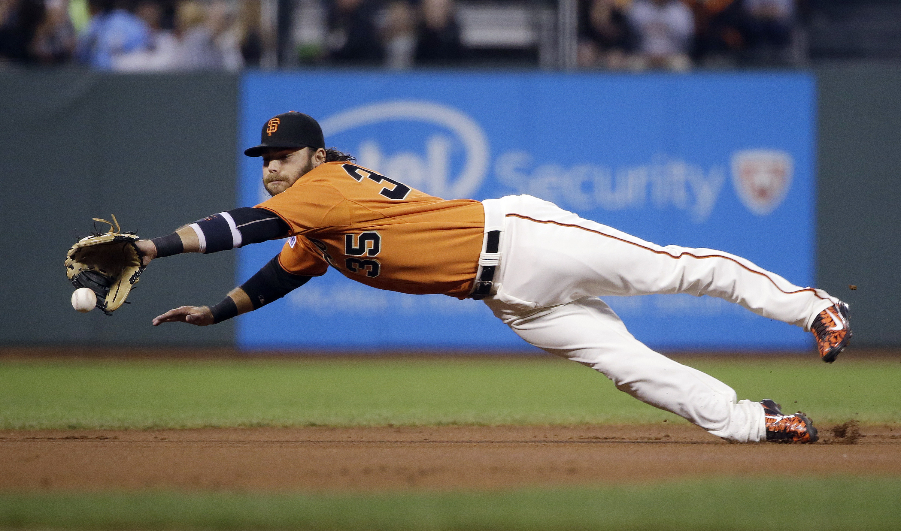 FILE - This Friday, Sept. 18, 2015 file photo San Francisco Giants shortstop Brandon Crawford makes a diving attempt at a ground ball by Arizona Diamondbacks' Paul Goldschmidt during the first inning of a baseball game in San Francisco. Fresh off his Gold