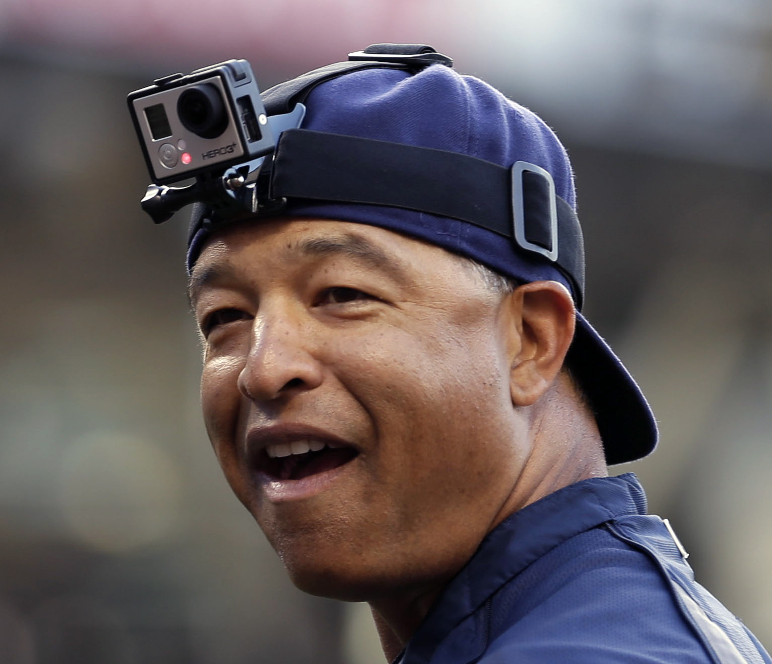 FILE - In this June 6, 2014, file photo, San Diego Padres bench coach Dave Roberts wears a GoPro camera on his head before receiving a ceremonial first pitch from GoPro founder and CEO Nick Woodman before the San Diego Padres played the Washington Nationa