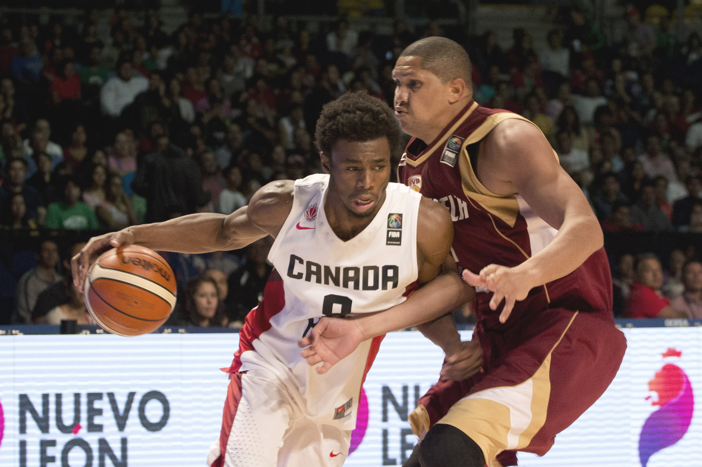Canada's Andrew Wiggins, left, controls the ball under pressure from Venezuela's Miguel Marriaga during a FIBA Americas Championship basketball game in Mexico City, Thursday Sept. 3, 2015. (AP Photo/Eduardo Verdugo)