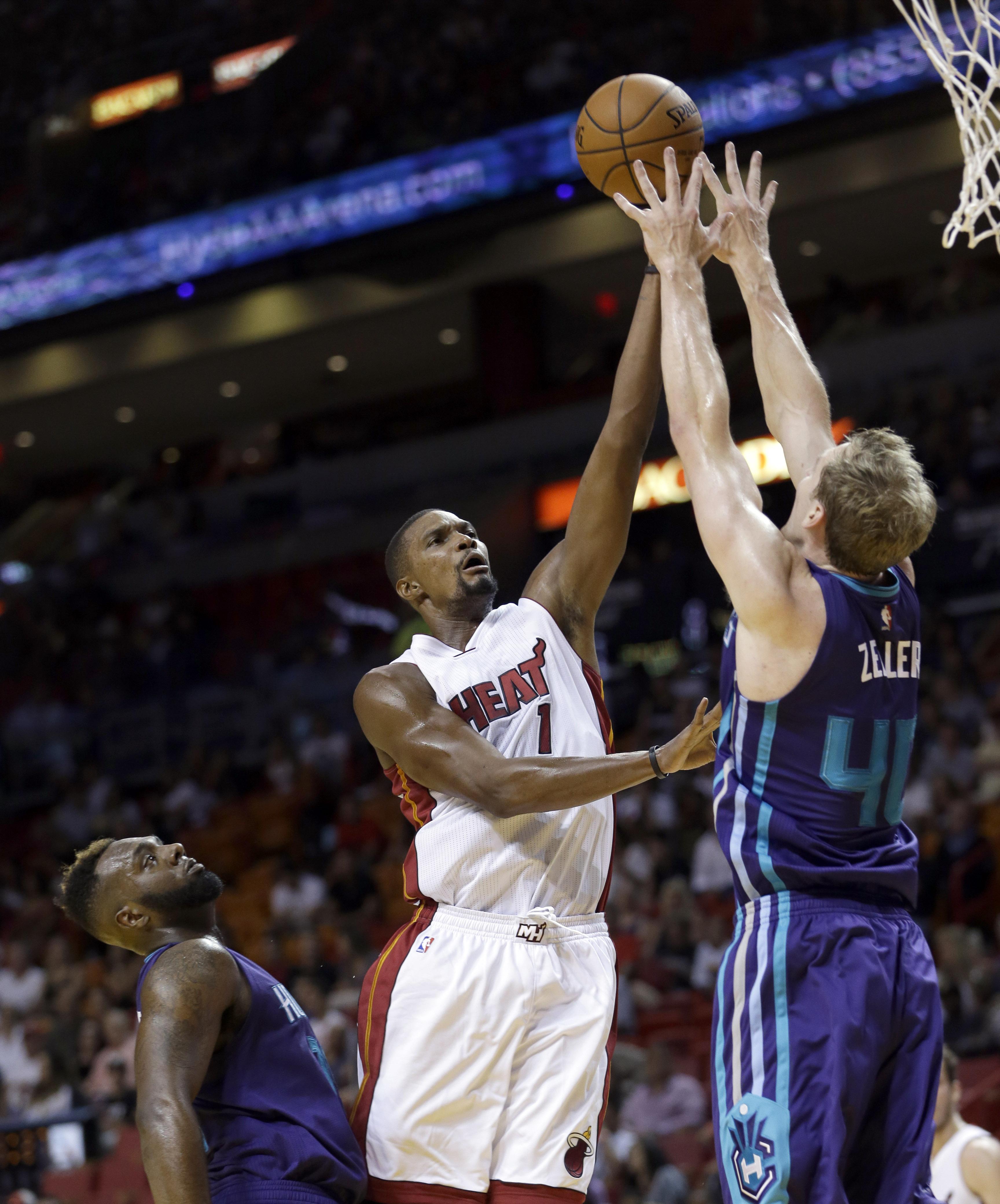 Miami Heat forward Chris Bosh (1) shoots against Charlotte Hornets forward Cody Zeller (40) in the first half of an NBA preseason basketball game, Sunday, Oct. 4, 2015, in Miami. The Hornets won 90-77. (AP Photo/Alan Diaz)