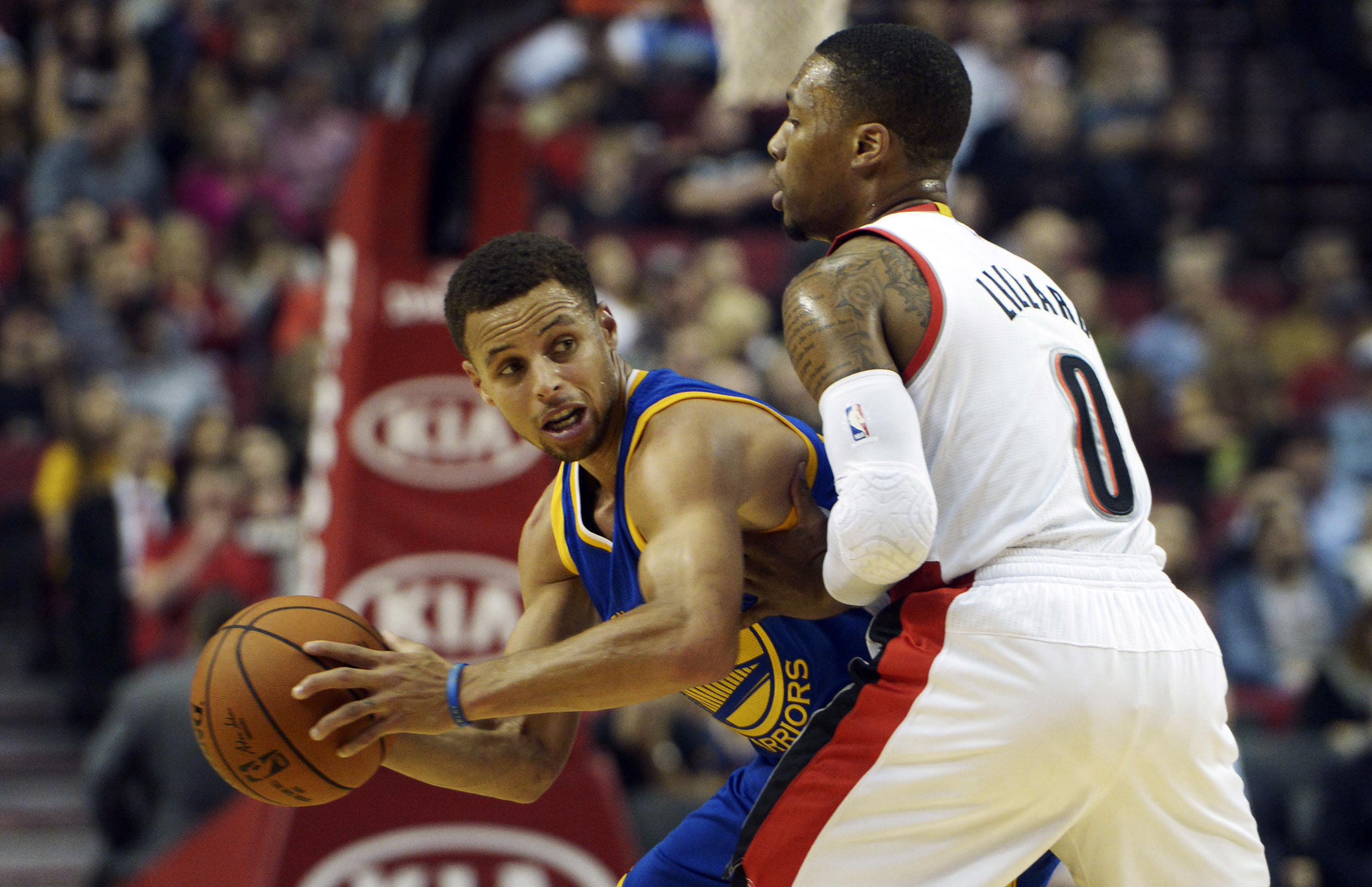 Golden State Warriors guard Stephen Curry, left, looks to pass the ball as Portland Trail Blazers guard Damian Lillard (0) defends during the first quarter of an NBA basketball game in Portland, Ore., Thursday, Oct. 8, 2015. (AP Photo/Steve Dykes)