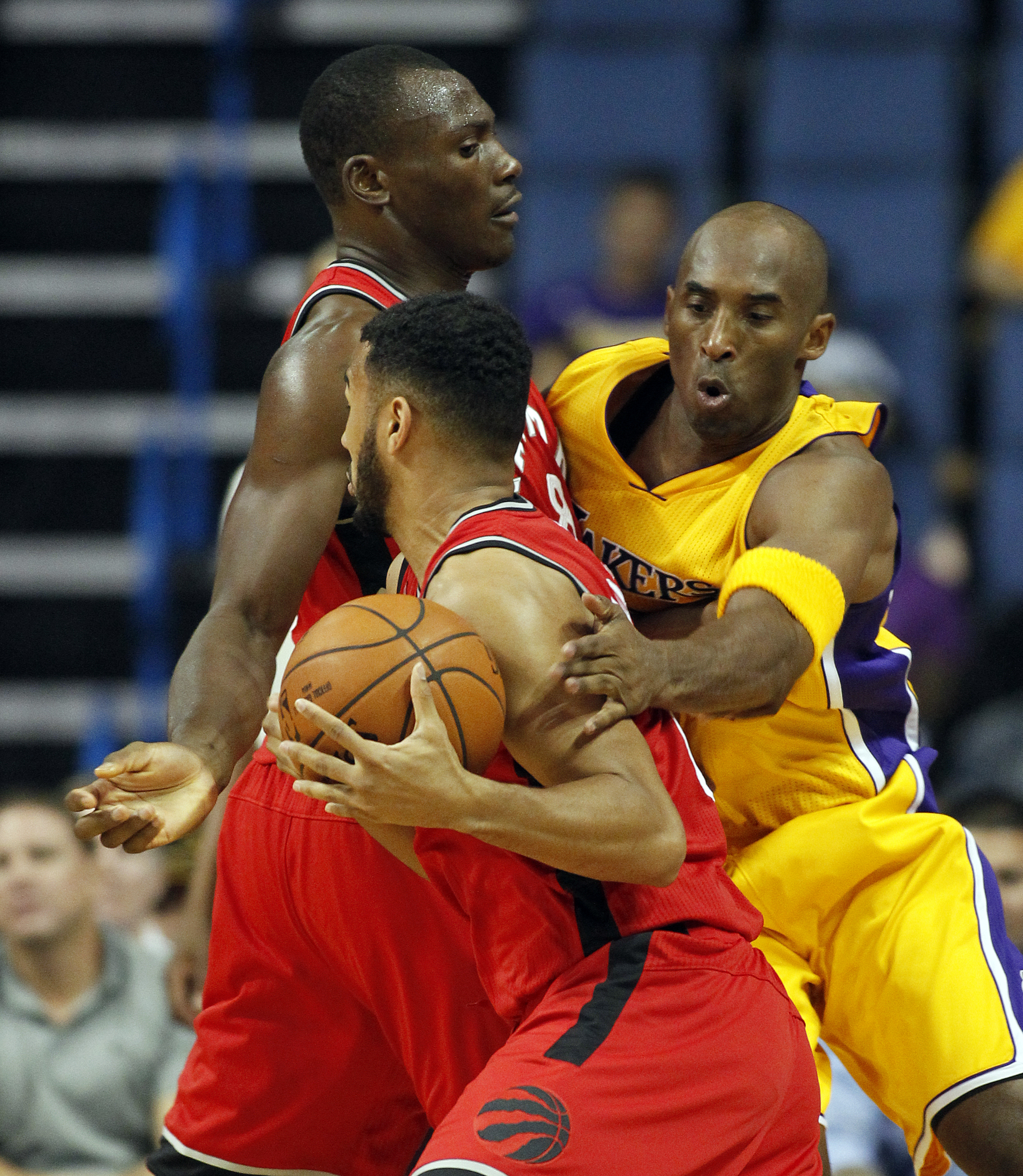 Toronto Raptors guard Cory Joseph, center, gets around a pick set by forward Bismack Biyombo, with Los Angeles Lakers guard Kobe Bryant, right, defending during the first half of an NBA preseason basketball game in Ontario, Calif., Thursday, Oct. 8, 2015.