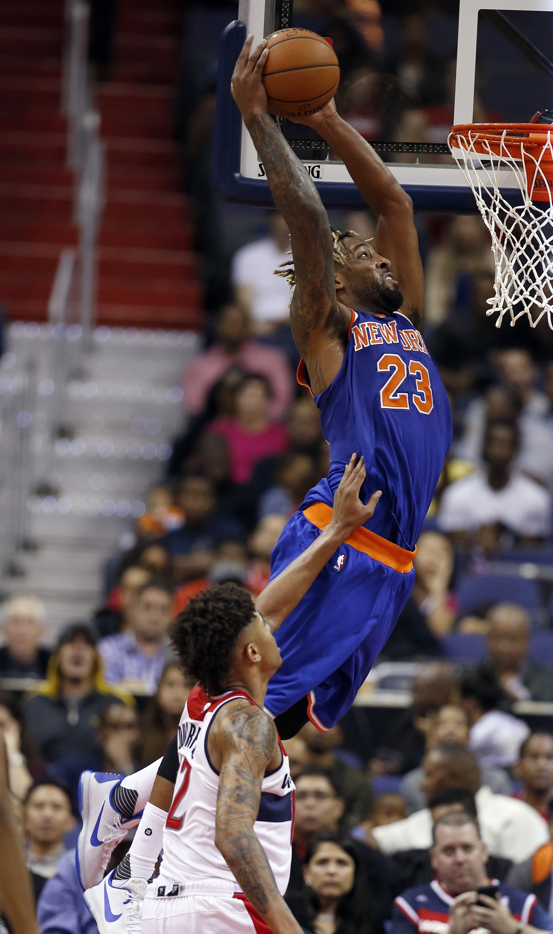New York Knicks forward Derrick Williams (23) dunks over Washington Wizards forward Kelly Oubre Jr. (12) in the second half of an NBA preseason basketball game, Friday, Oct. 9, 2015, in Washington. The Knicks won 115-104. (AP Photo/Alex Brandon)