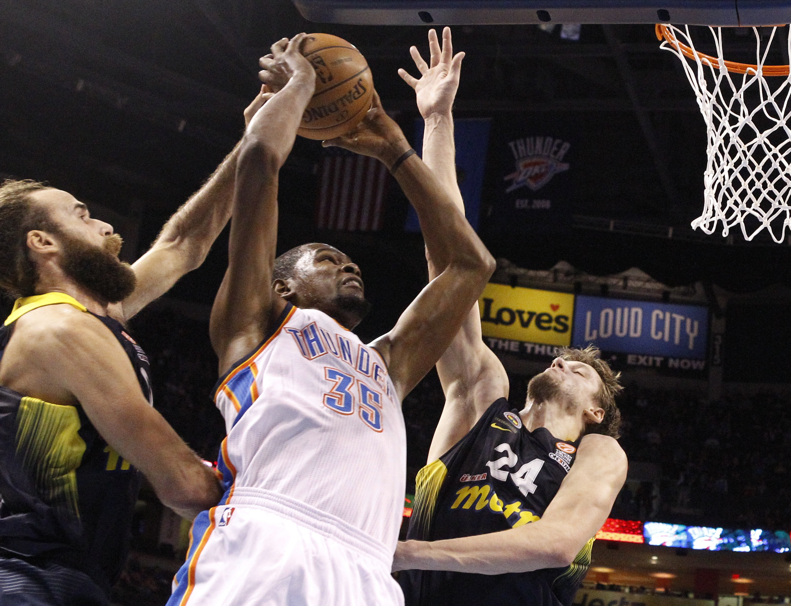 Oklahoma City Thunder forward Kevin Durant (35) shoots between Fenerbahce Ulker's Luigi Datome, left, and Jan Vesely (24) in the first quarter of an NBA basketball preseason game in Oklahoma City, Friday, Oct. 9, 2015. (AP Photo/Sue Ogrocki)