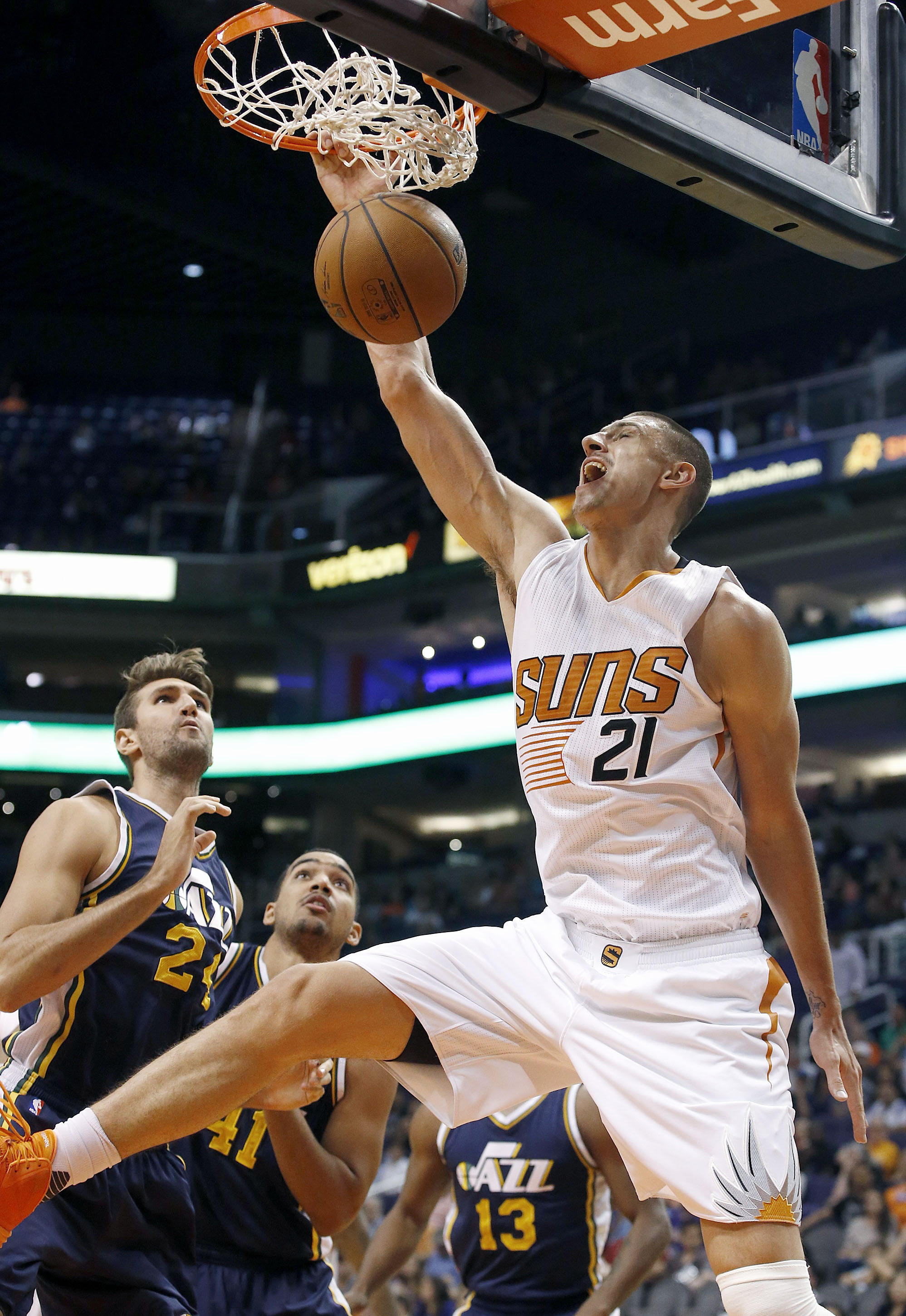 Phoenix Suns' Alex Len (21), of Ukraine, dunks as Utah Jazz's Jeff Withey, left, and Trey Lyles (41) watch during the first half of an NBA preseason basketball game Friday, Oct. 9, 2015, in Phoenix. (AP Photo/Ross D. Franklin)