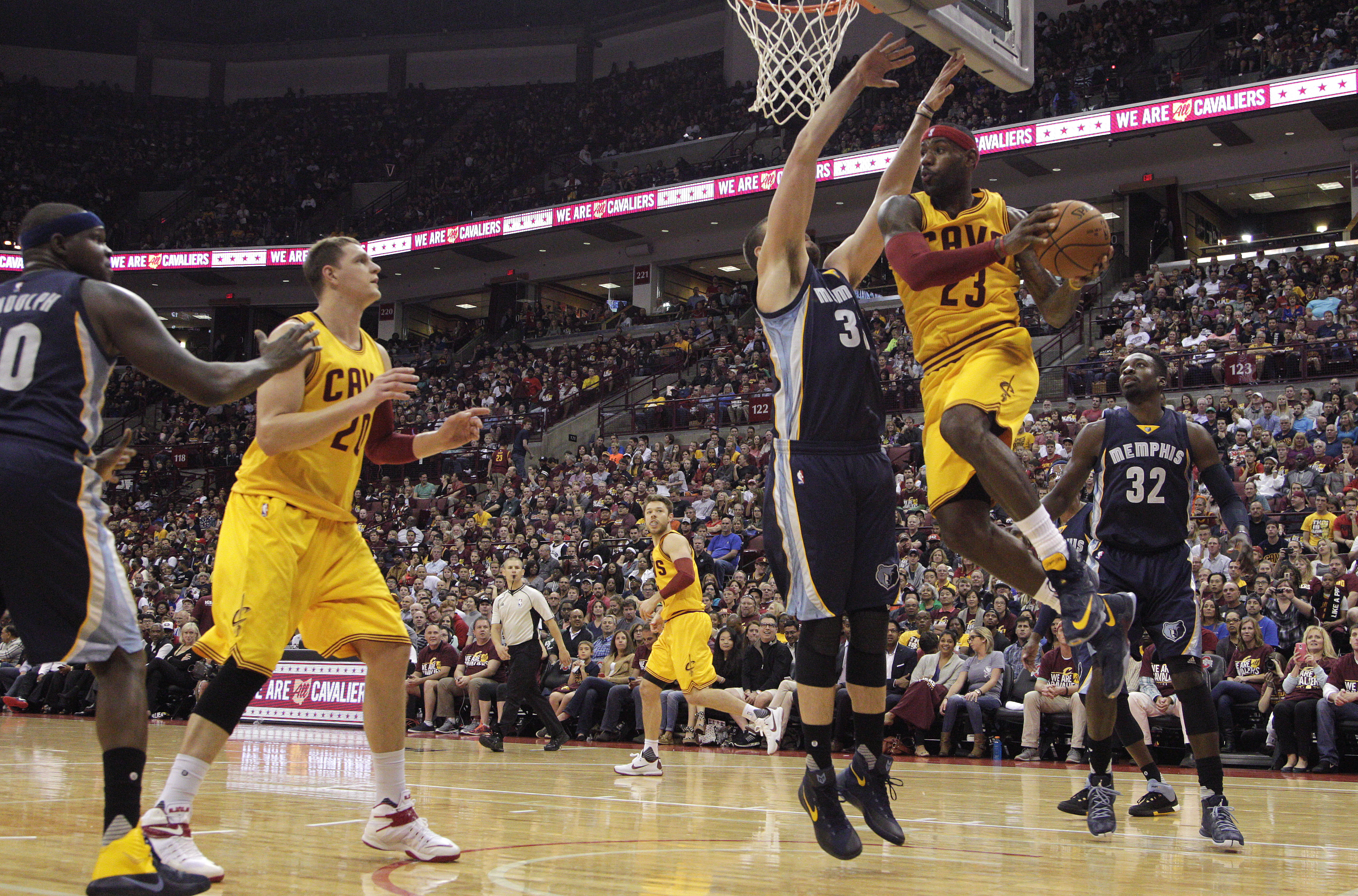 Cleveland Cavaliers' LeBron James (23) drives to the basket between Memphis Grizzlies' Jeff Green, right, and Marc Gasol, of Spain, during the second quarter of an NBA preseason basketball game Monday, Oct. 12, 2015, in Columbus, Ohio. (AP Photo/Jay LaPre