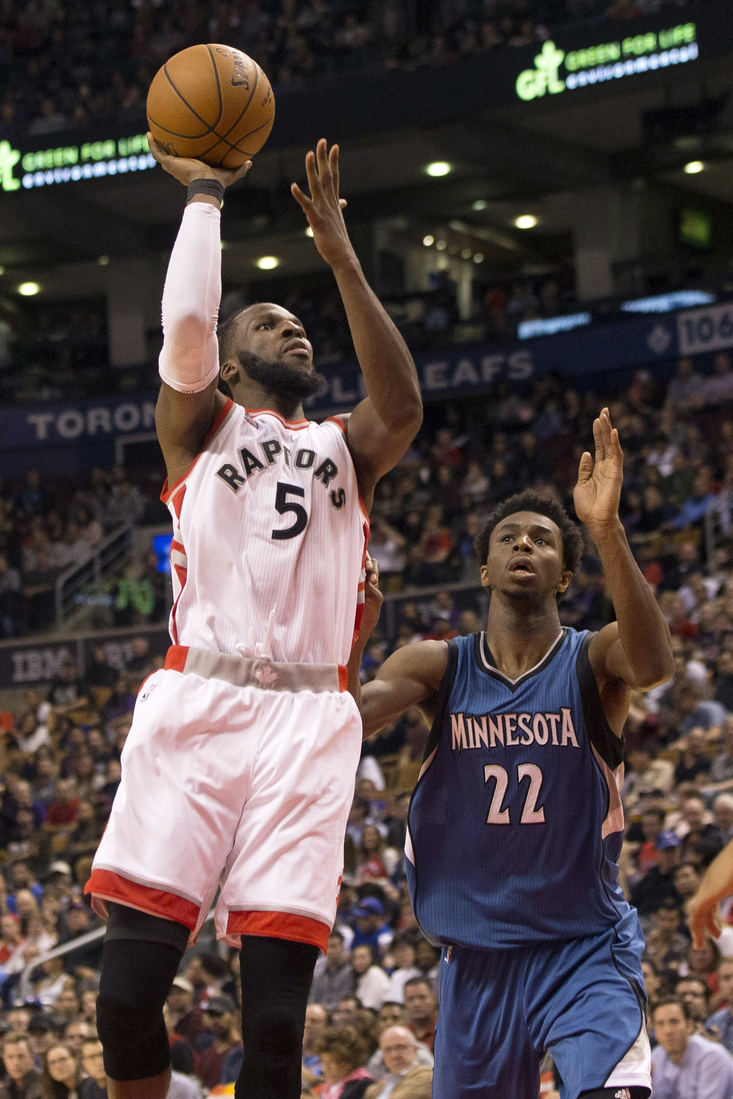Toronto Raptors' DeMarre Carroll, left, shoots against Minnesota Timberwolves' Andrew Wiggins during the first half of an NBA preseason basketball game Monday, Oct. 12, 2015, in Toronto. (Chris Young/The Canadian Press via AP) MANDATORY CREDIT