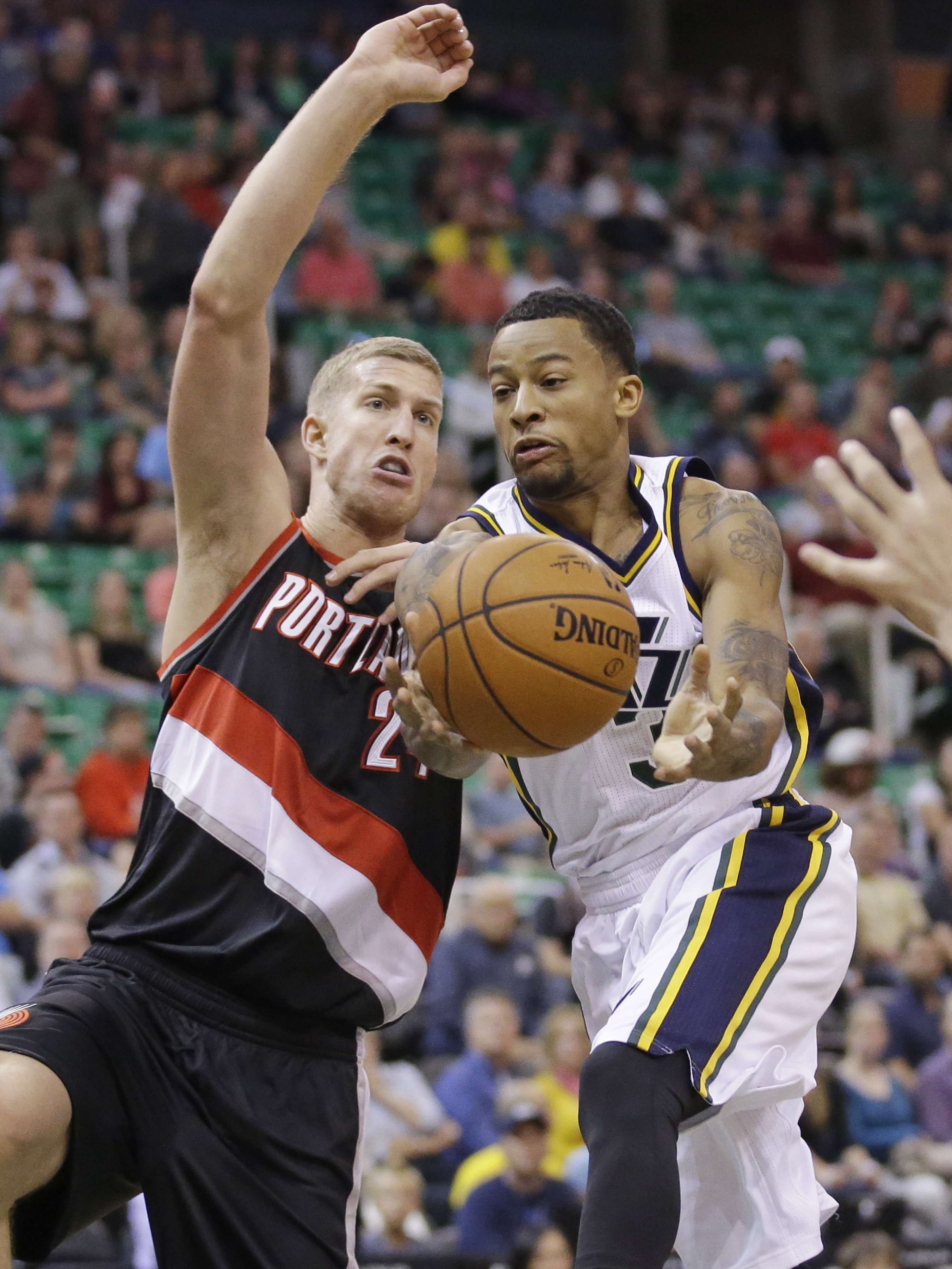 Utah Jazz guard Trey Burke, right, goes to the basket as Portland Trail Blazers forward Mason Plumlee (24) defends during the first quarter of an NBA preseason basketball game Monday, Oct. 12, 2015, in Salt Lake City. (AP Photo/Rick Bowmer)