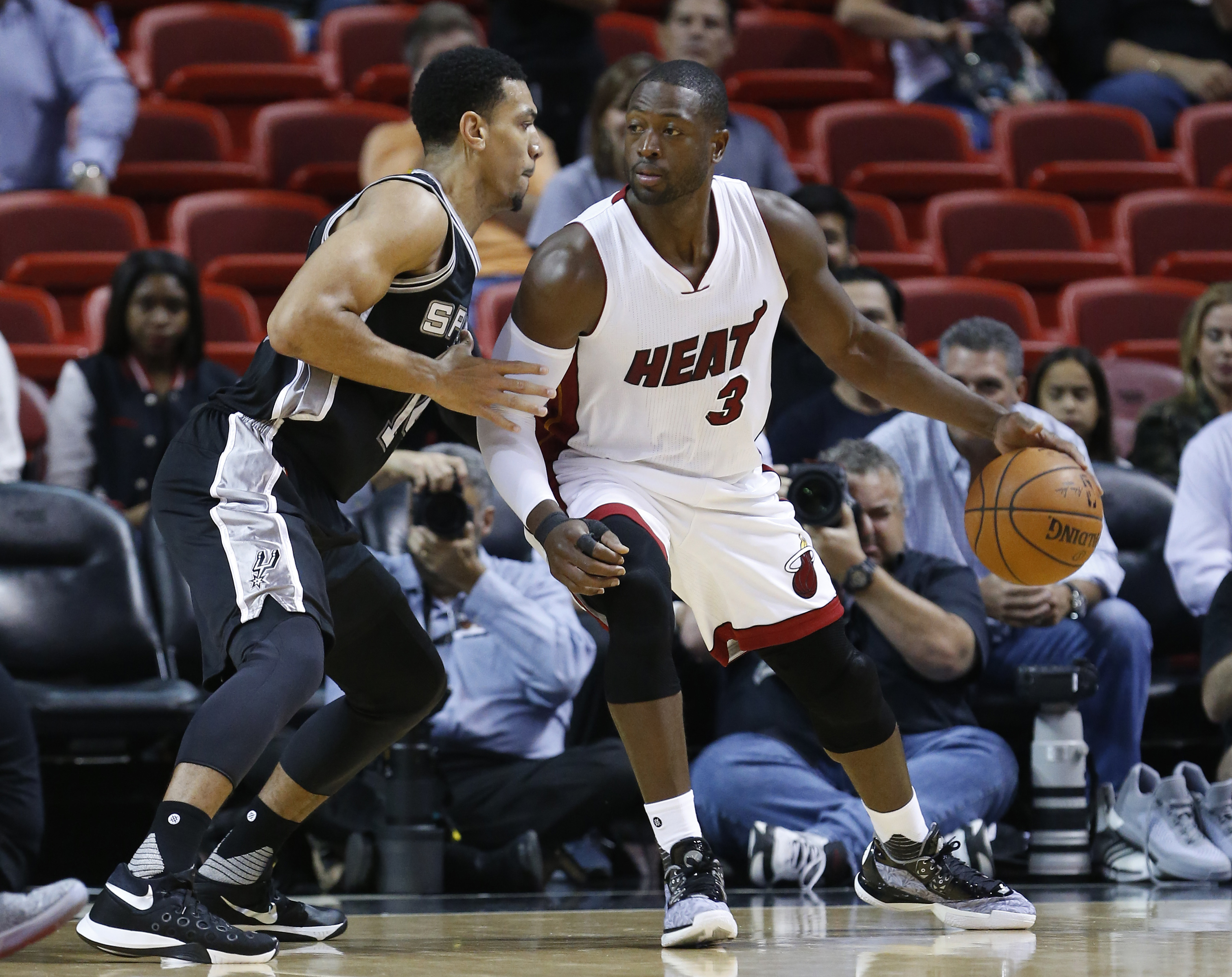 Miami Heat guard Dwyane Wade (3) looks for an opening past San Antonio Spurs guard Danny Green during the first half of a preseason NBA basketball game, Monday, Oct. 12, 2015, in Miami. Wade had 16 points as the Heat defeated the Spurs 97-94. (AP Photo/Wi