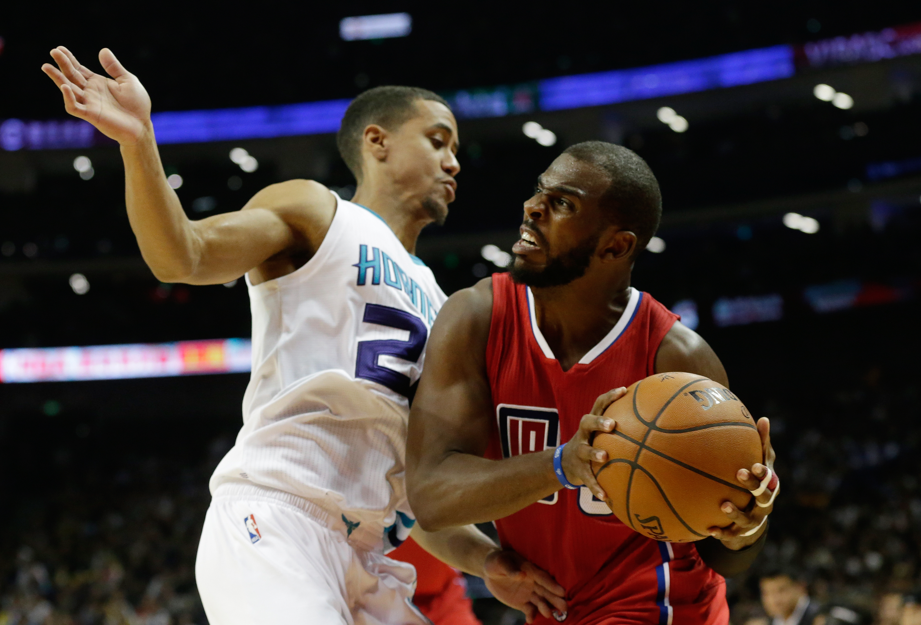 NBA Los Angeles Clippers' Chris Paul, right, tries to pass through Brian Roberts of Charlotte Hornets during the NBA Global Games at the Mercedes-Benz Arena in Shanghai, China, Wednesday, Oct. 14, 2015. (AP Photo/Andy Wong)