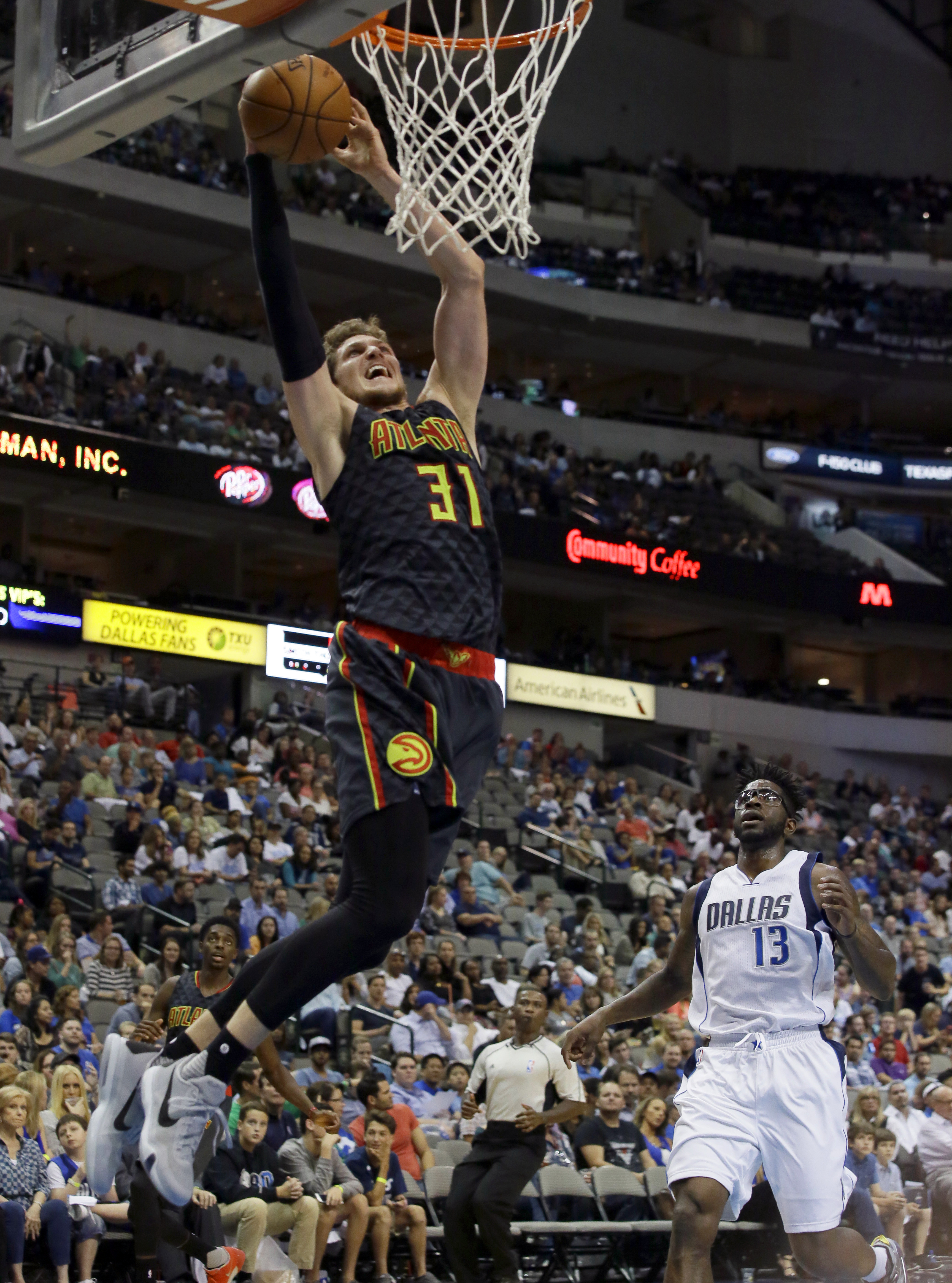 Atlanta Hawks forward Mike Muscala (31) scores in front of Dallas Mavericks forward Jamil Wilson (13) during the second half of a preseason NBA basketball game Friday, Oct. 16, 2015, in Dallas. The Hawks won 91-84. (AP Photo/LM Otero)