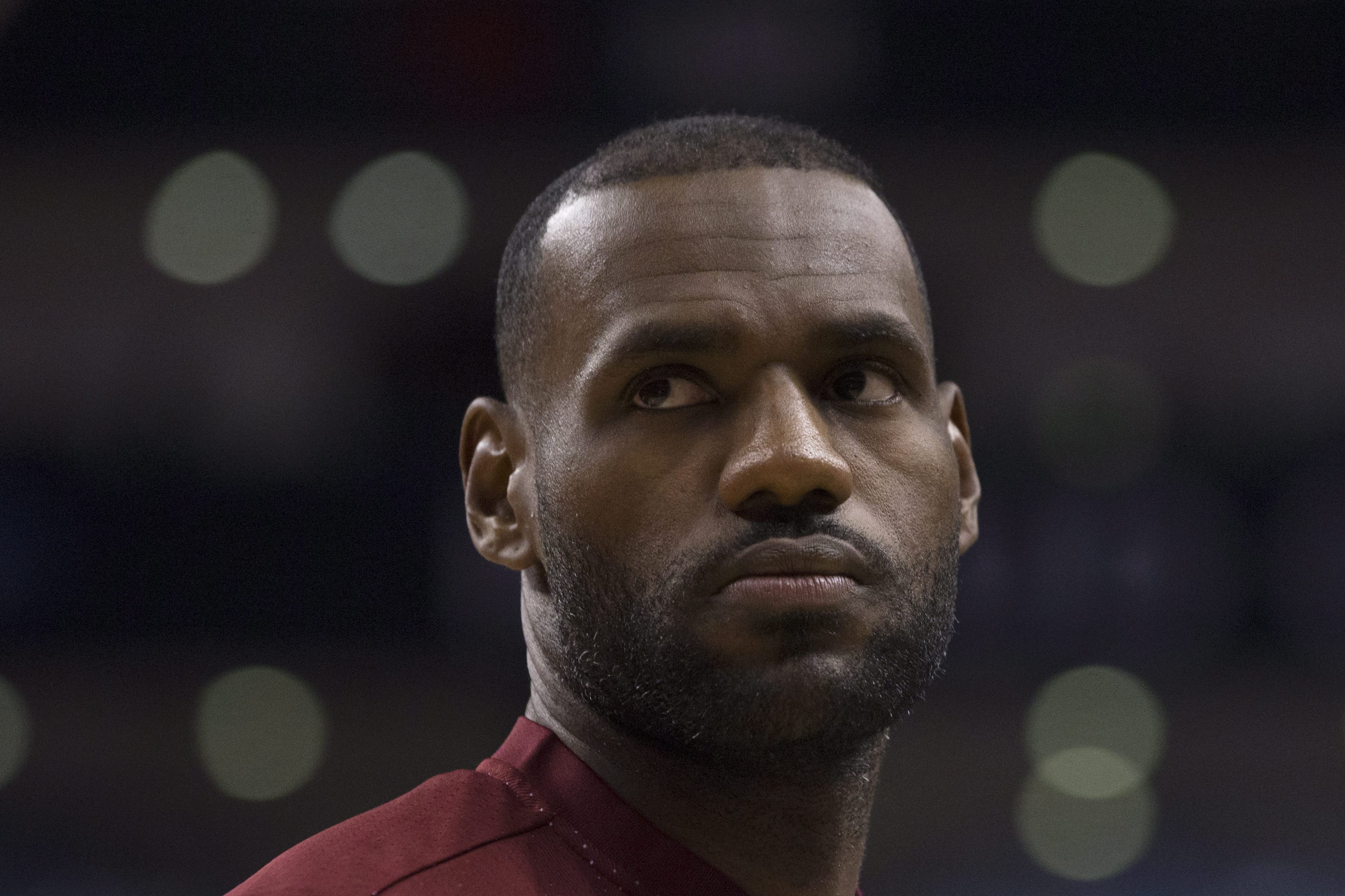 Cleveland Cavaliers' LeBron James stands on the edge of a team huddle during a timeout in first half of an NBA preseason basketball game against the Toronto Raptors in Toronto on Sunday, Oct. 18, 2015. (Chris Young/The Canadian Press via AP)