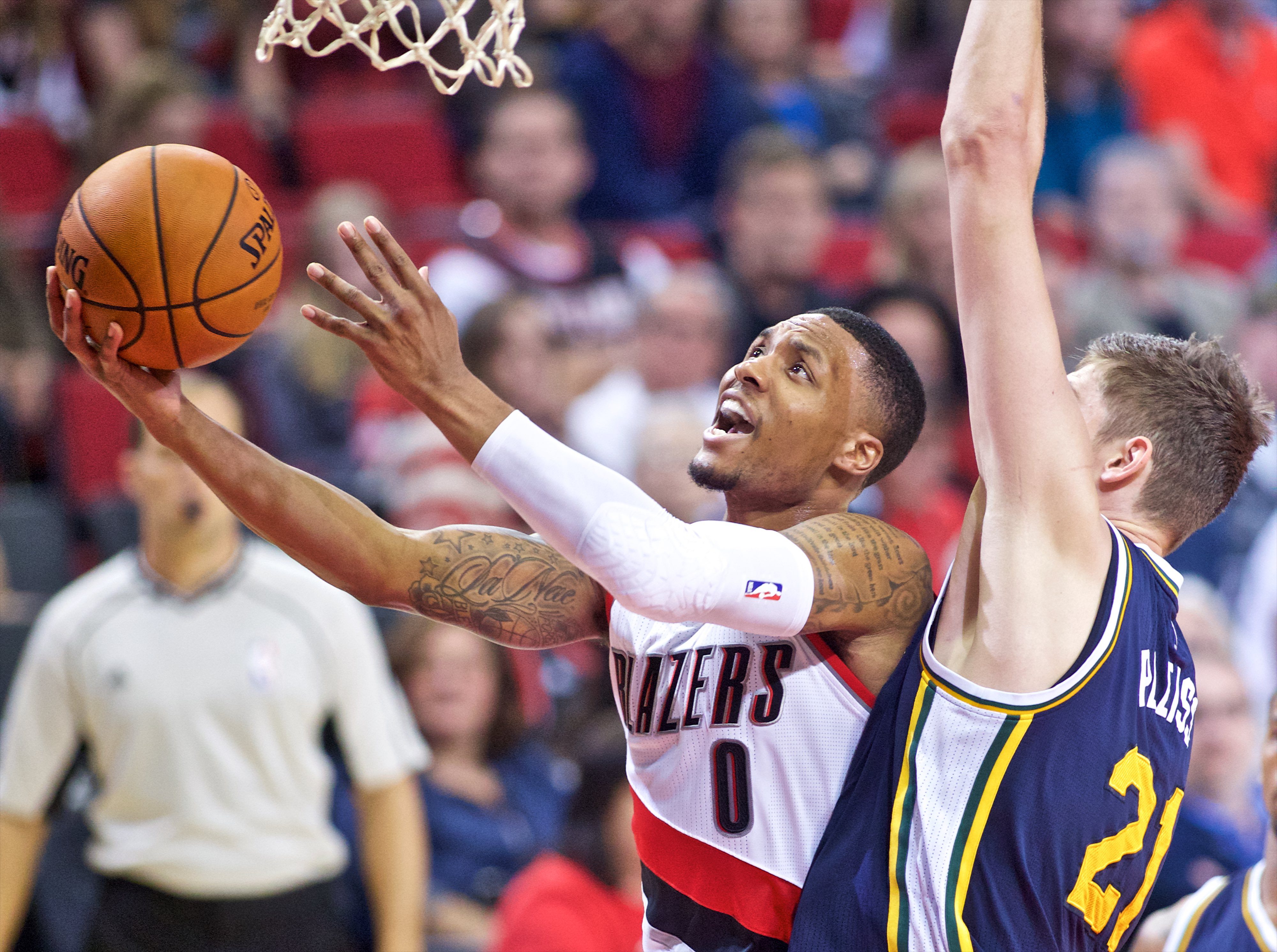 Portland Trail Blazers guard Damian Lillard, left, shoots over Utah Jazz center Tibor Pleiss during the first half of an NBA preseason basketball game in Portland, Ore., Sunday, Oct. 18, 2015. (AP Photo/Craig Mitchelldyer)
