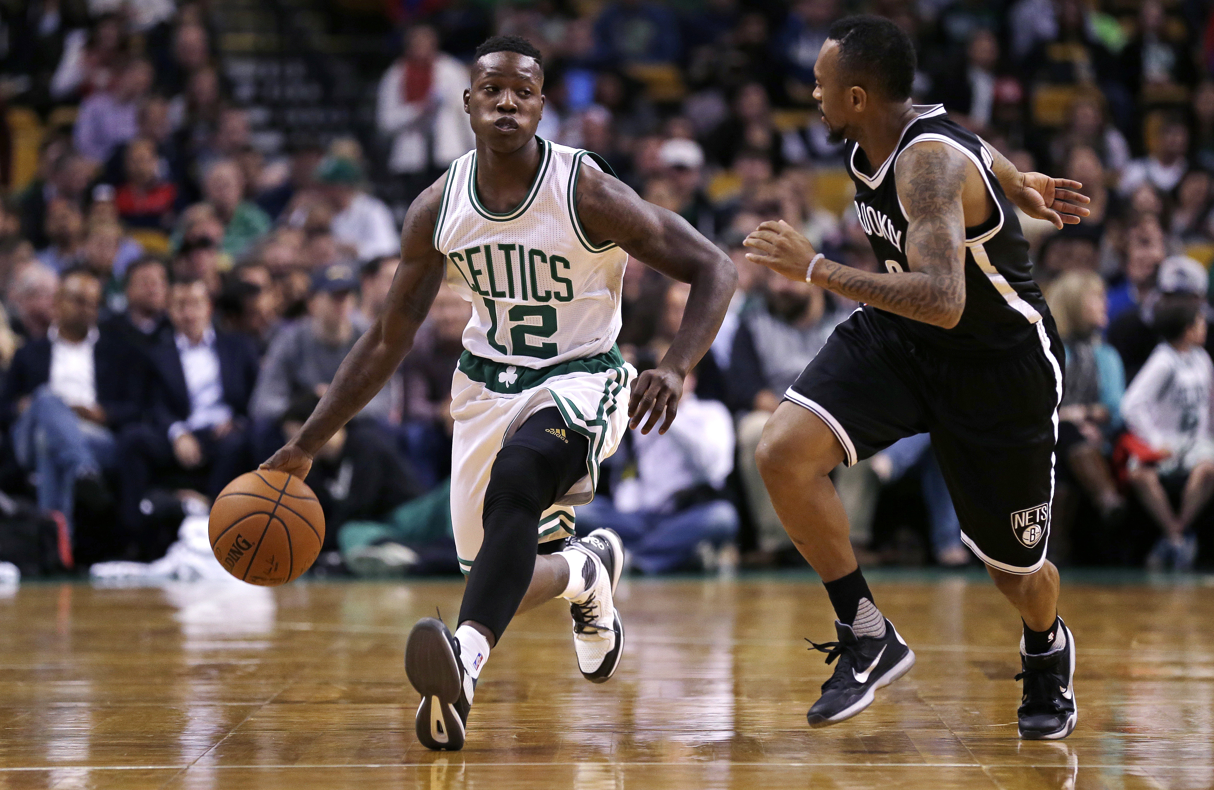 Boston Celtics guard Terry Rozier (12) tries to outrun Brooklyn Nets guard Ryan Boatright, right, while bringing the ball up court during the first half of an NBA preseason basketball game in Boston, Monday, Oct. 19, 2015. (AP Photo/Charles Krupa)
