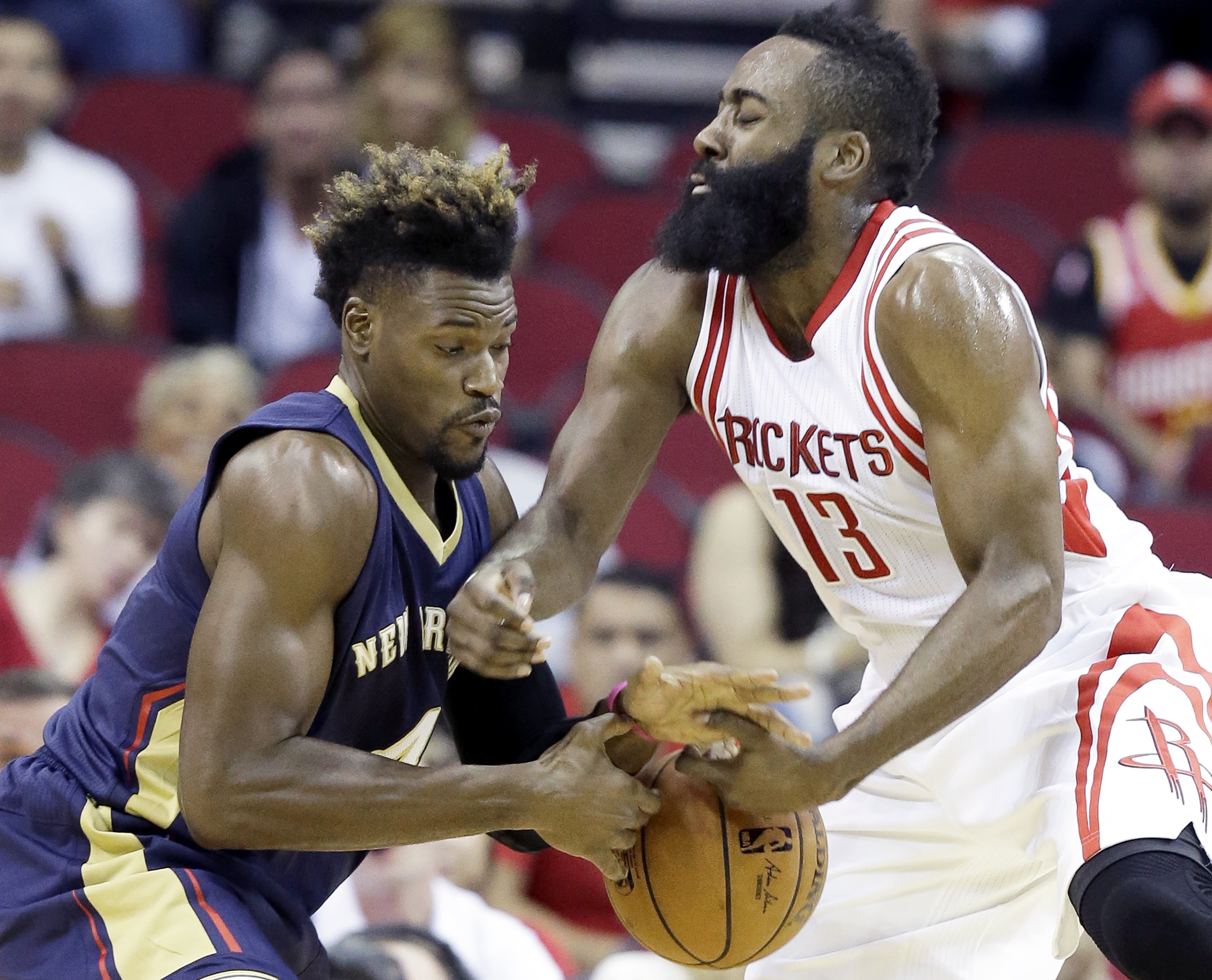 Houston Rockets' James Harden (13) and New Orleans Pelicans' Jeff Adrien grab for the ball in the first half of a preseason NBA basketball game Monday, Oct. 19, 2015, in Houston. (AP Photo/Pat Sullivan)