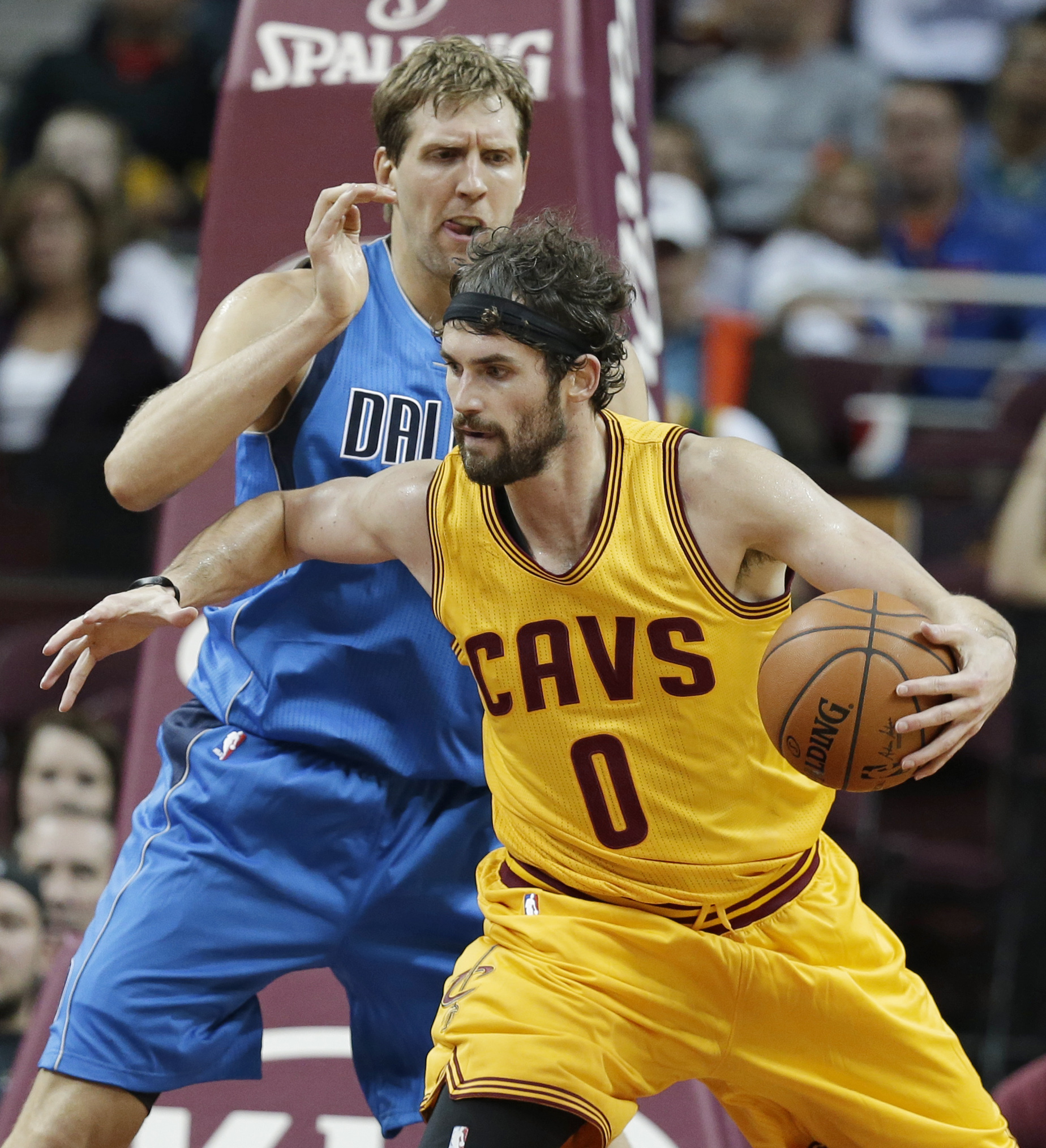 Cleveland Cavaliers' Kevin Love, right, drives past Dallas Mavericks' Dirk Nowitzki, from Germany, in the second half of an NBA preseason basketball game Monday, Oct. 19, 2015, in Cleveland. The Cavaliers won 103-97. (AP Photo/Tony Dejak)