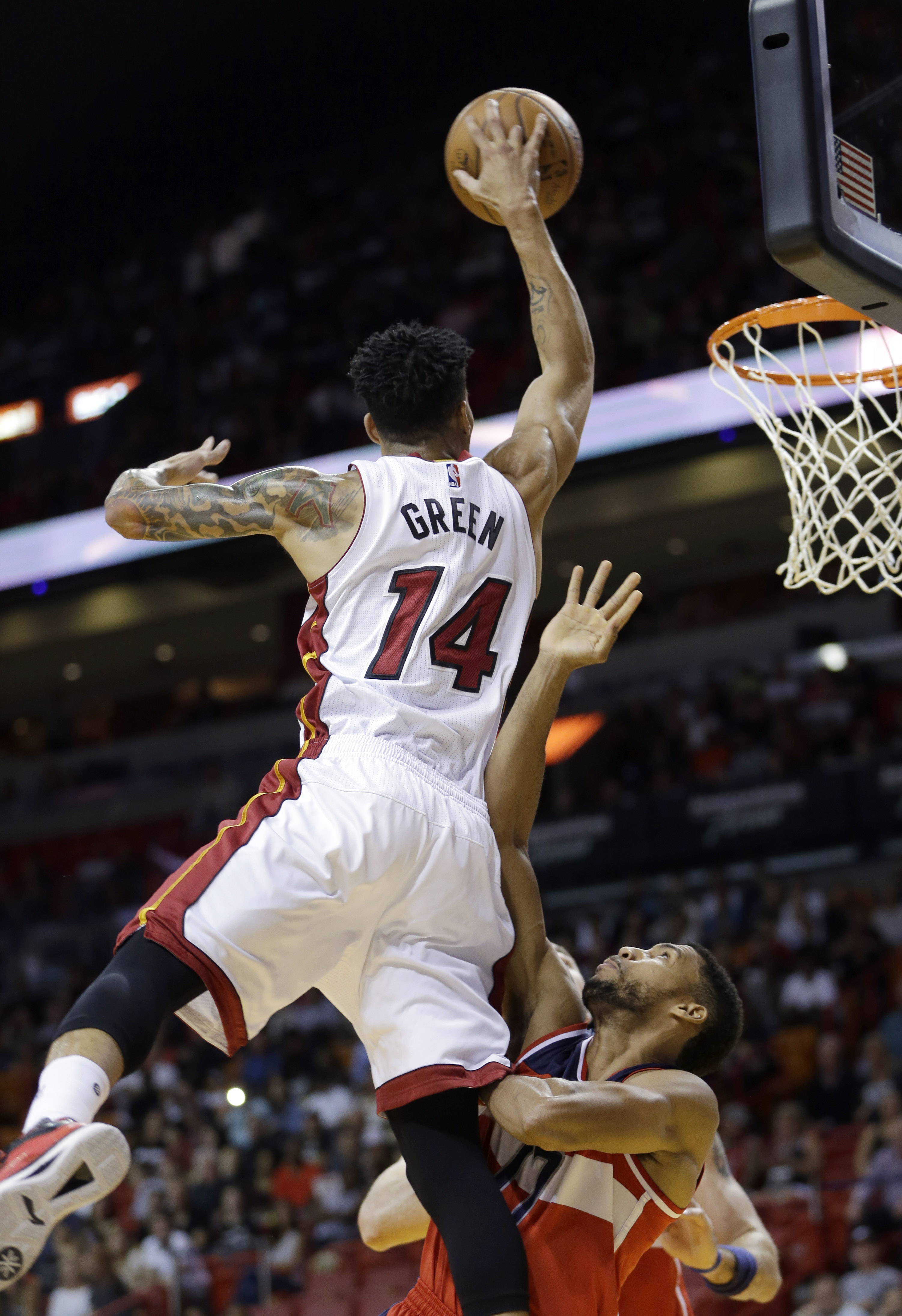 Miami Heat guard Gerald Green (14) is fouled as he goes to the basket by Washington Wizards guard Garrett Temple (17)  in the first half of an NBA preseason basketball game, Wednesday, Oct. 21, 2015, in Miami. (AP Photo/Alan Diaz)