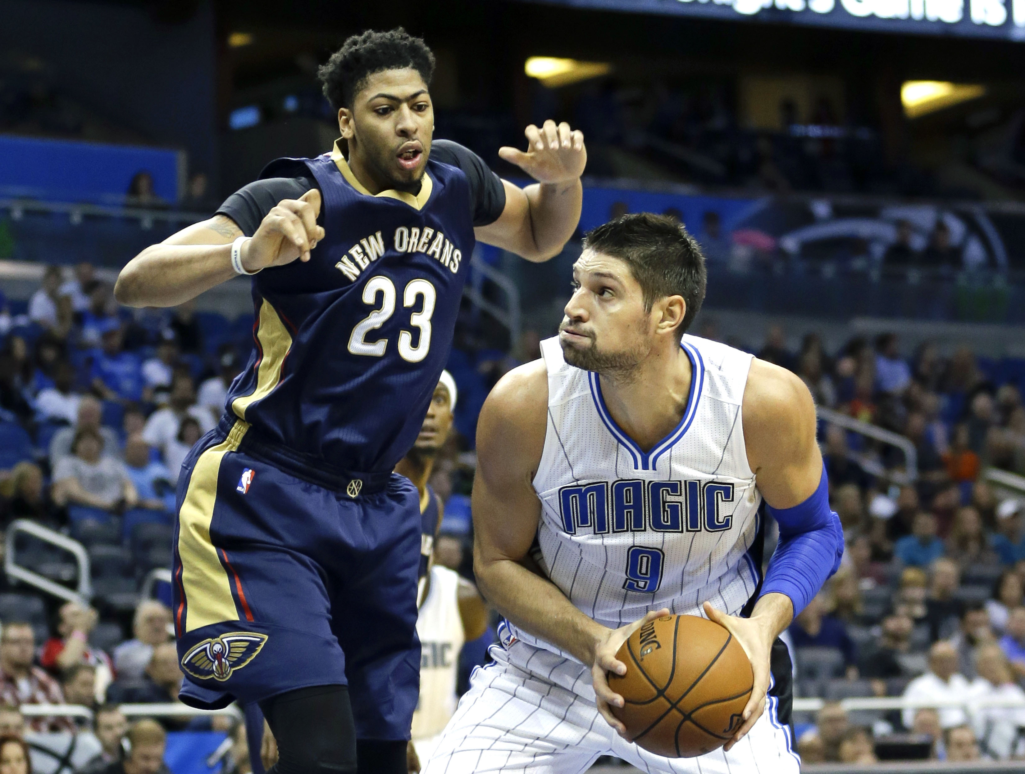 Orlando Magic's Nikola Vucevic (9) looks for a shot as he is guarded by New Orleans Pelicans' Anthony Davis (23) during the second half of an NBA preseason basketball game, Wednesday, Oct. 21, 2015, in Orlando, Fla. Orlando won in overtime 110-107. (AP Ph