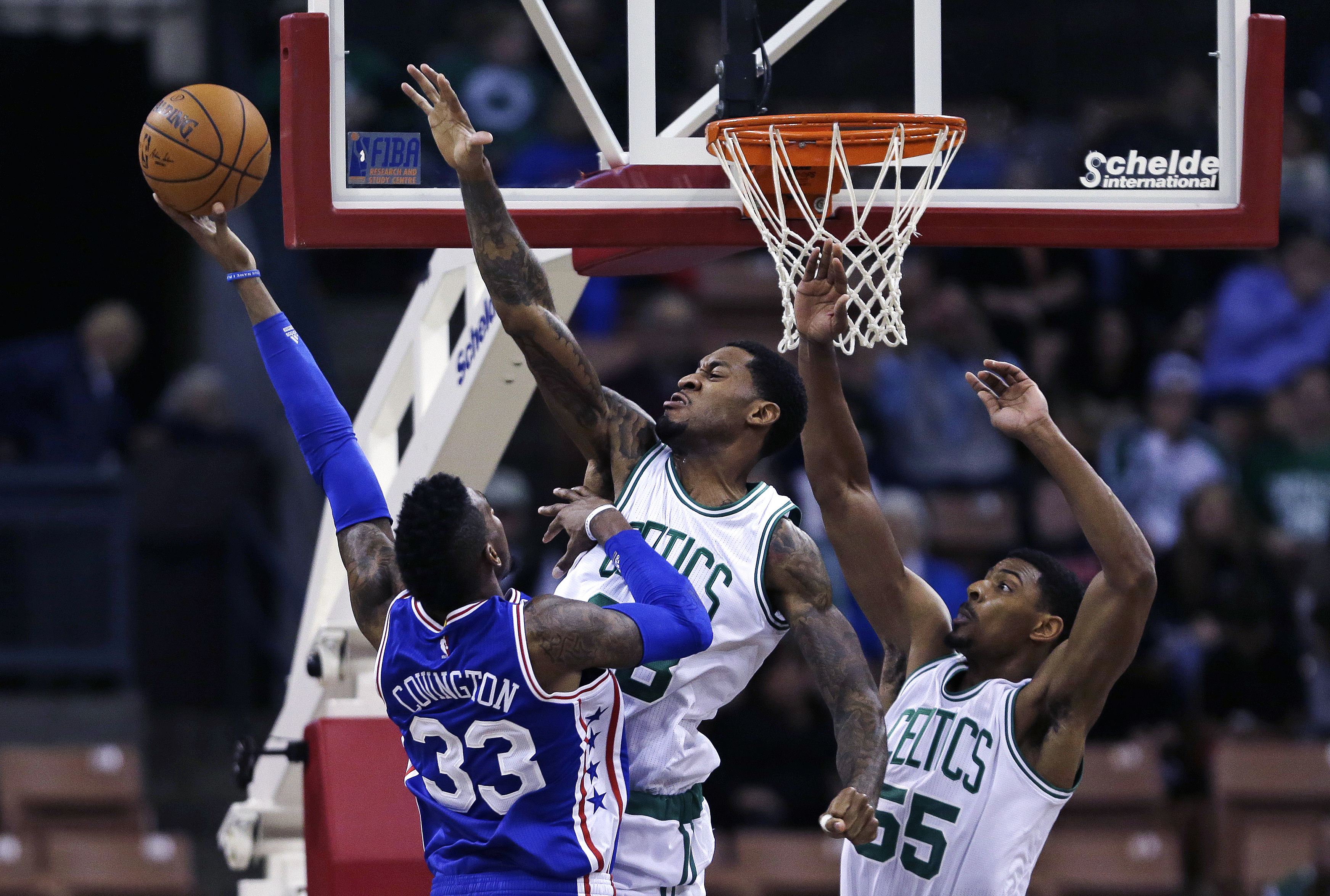 Philadelphia 76ers forward Robert Covington (33) is fouled by Boston Celtics forward Perry Jones, center, while driving to the basket during the second half of a preseason NBA basketball game in Manchester, N.H., Friday, Oct. 23, 2015. Covington was helpe