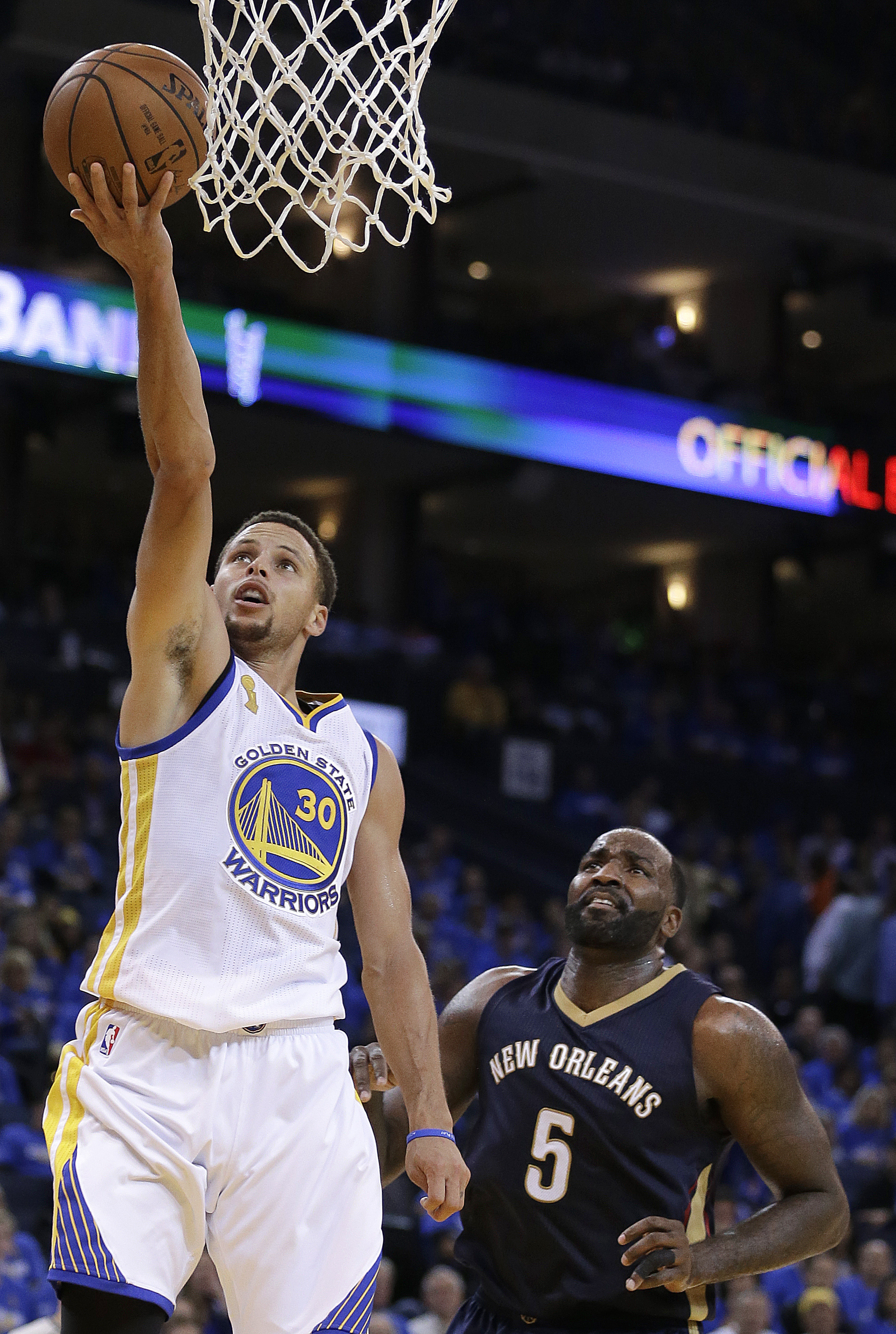 Golden State Warriors' Stephen Curry, left, lays up a shot in front of New Orleans Pelicans' Kendrick Perkins (5) during the second half of an NBA basketball game Tuesday, Oct. 27, 2015, in Oakland, Calif. (AP Photo/Ben Margot)