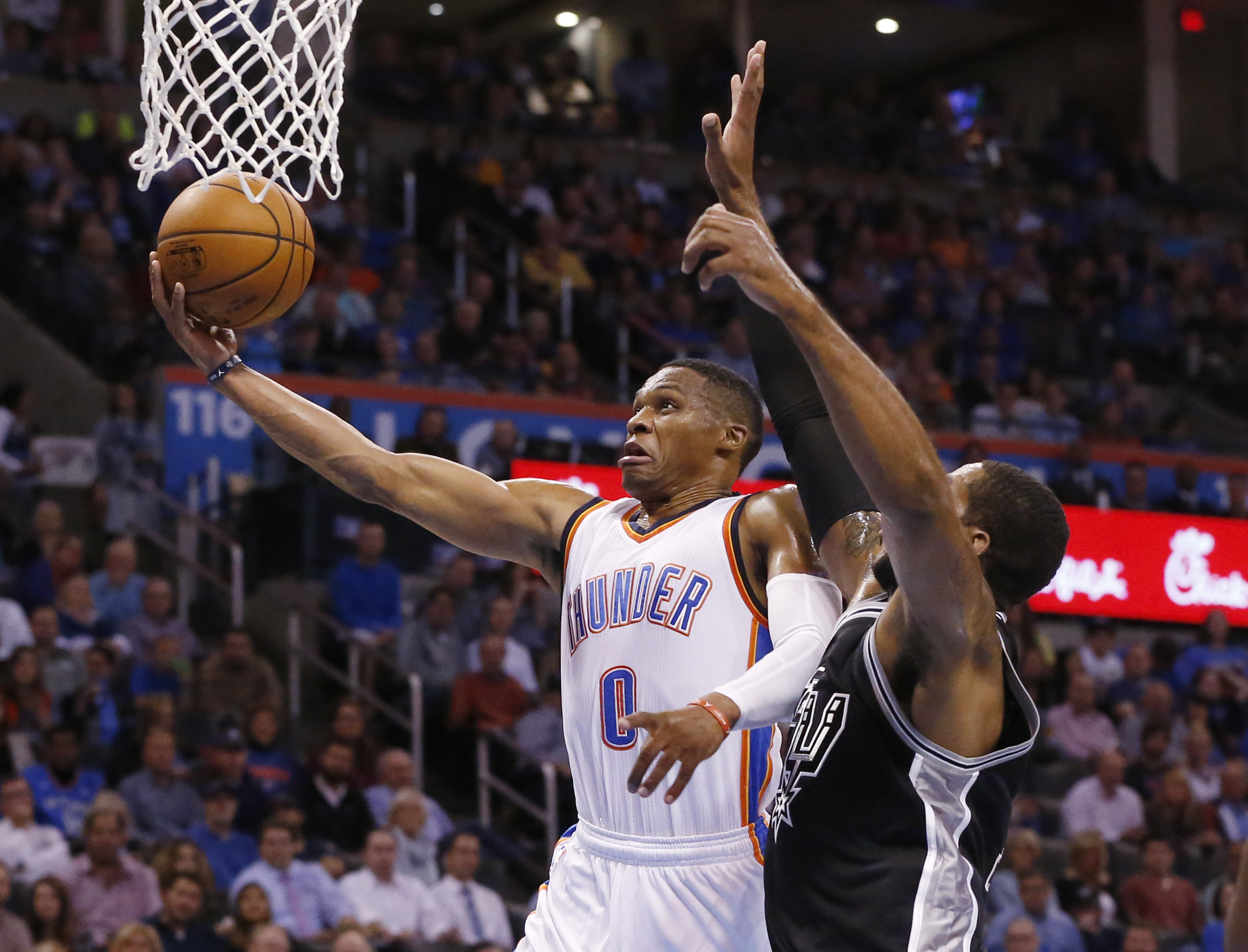 Oklahoma City Thunder guard Russell Westbrook (0) shoots in front of San Antonio Spurs forward LaMarcus Aldridge, right, in the first quarter of an NBA basketball game in Oklahoma City, Wednesday, Oct. 28, 2015. (AP Photo/Sue Ogrocki)
