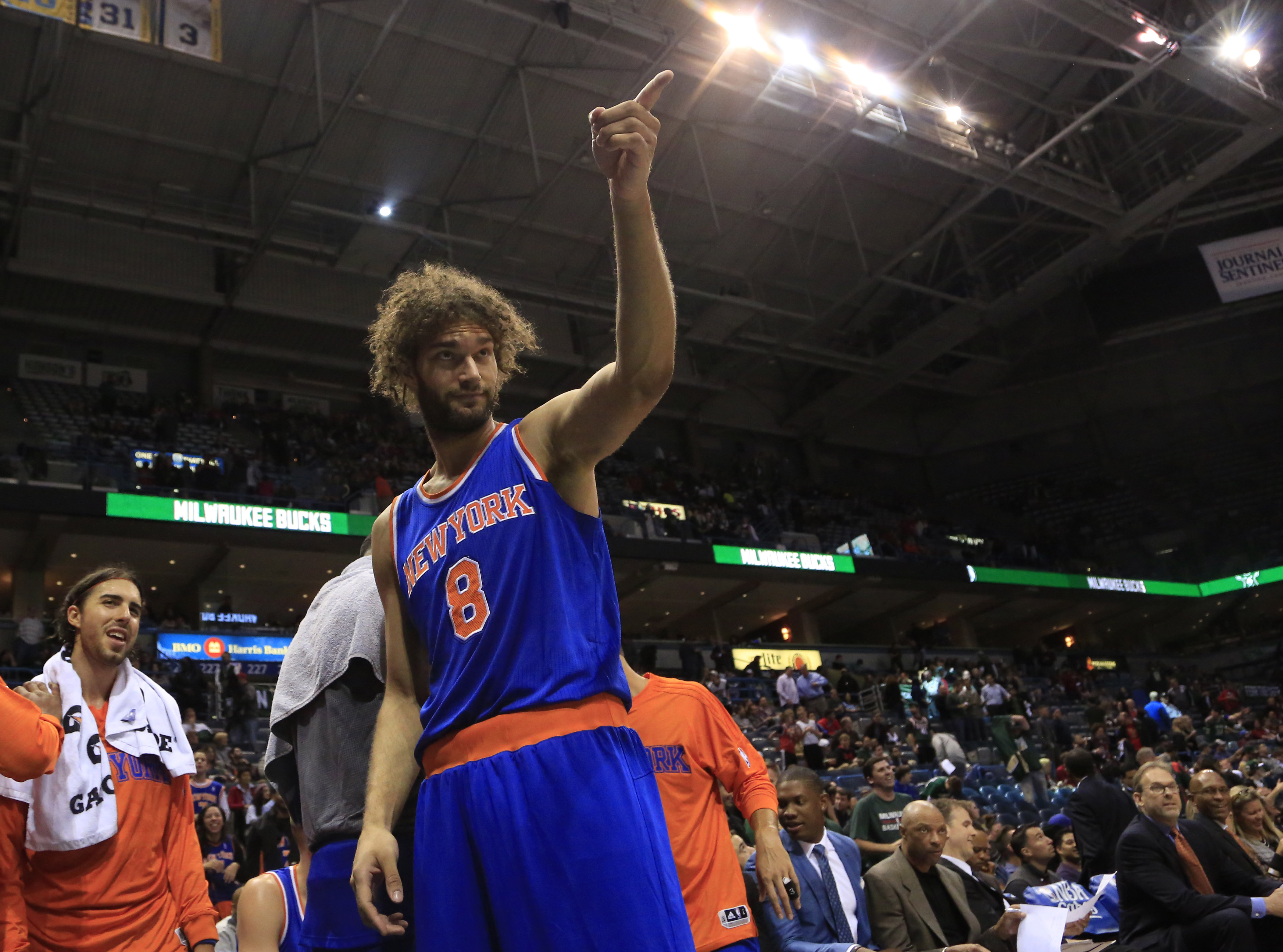 New York Knicks center Robin Lopez points at Bango the Milwaukee Bucks mascot at the end of an NBA basketball game Wednesday, Oct. 28, 2015, in Milwaukee. The Knicks defeated the Bucks 122-97. (AP Photo/Darren Hauck)
