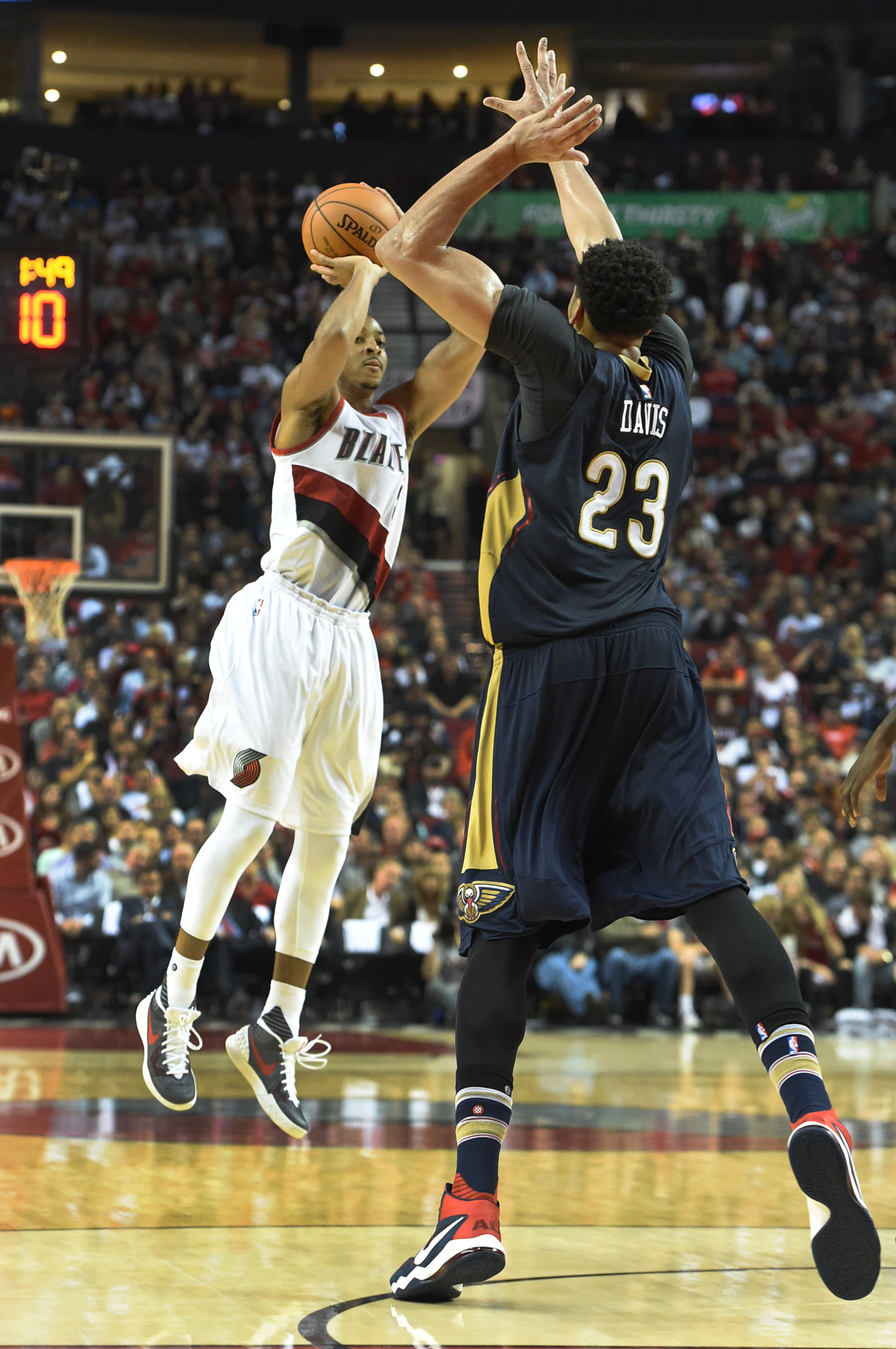 Portland Trail Blazers guard C.J. McCollum (3) hits a shot over New Orleans Pelicans forward Anthony Davis (23) during the fourth quarter of an NBA basketball game in Portland, Ore., Wednesday, October 28, 2015. (AP Photo/Steve Dykes)
