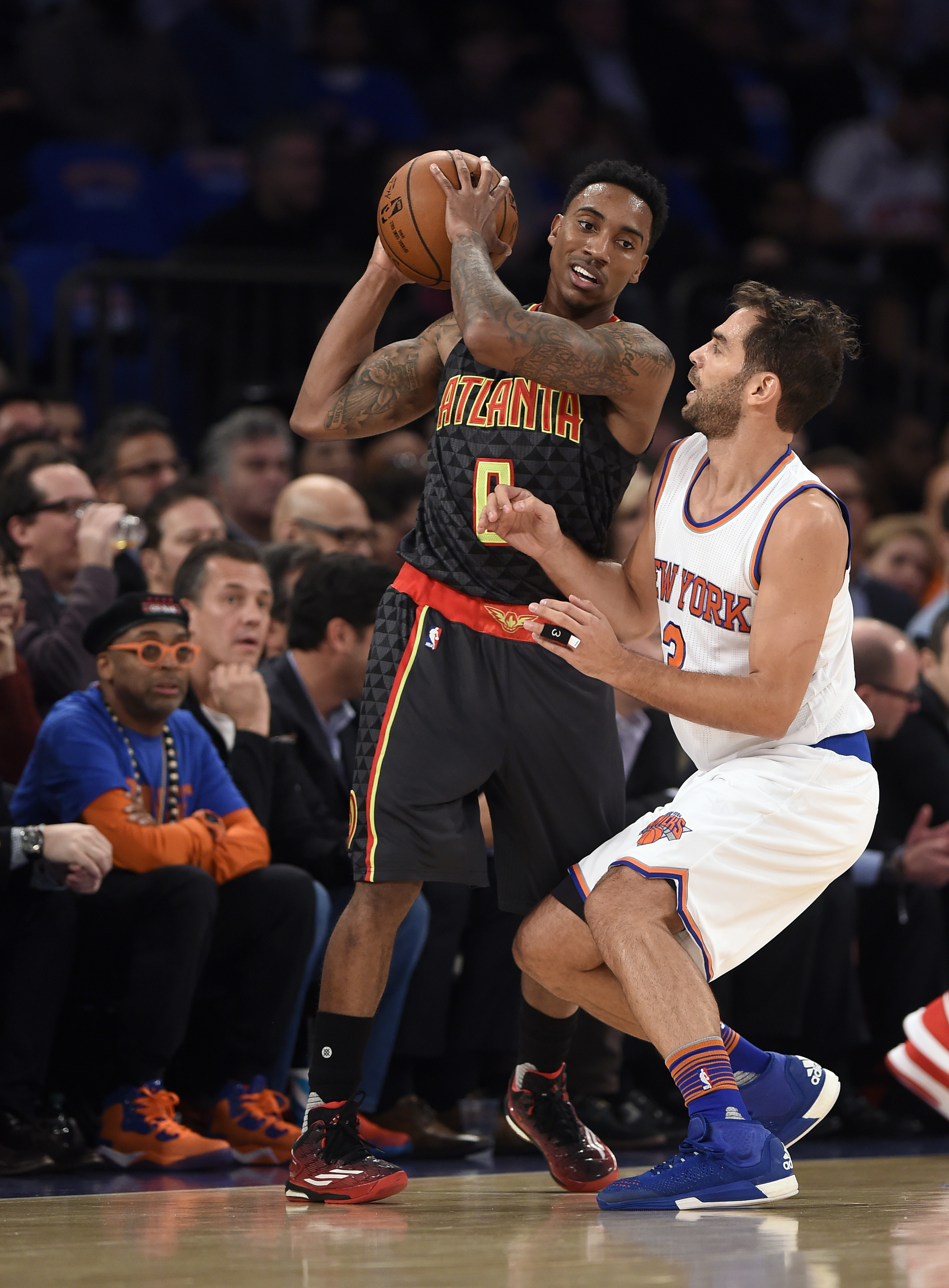 Atlanta Hawks guard Jeff Teague (0) keeps the ball away from New York Knicks guard Jose Calderon (3) as film director Spike Lee, left, watches during the first half of an NBA basketball game on Thursday, Oct. 29, 2015, in New York. (AP Photo/Kathy Kmonice