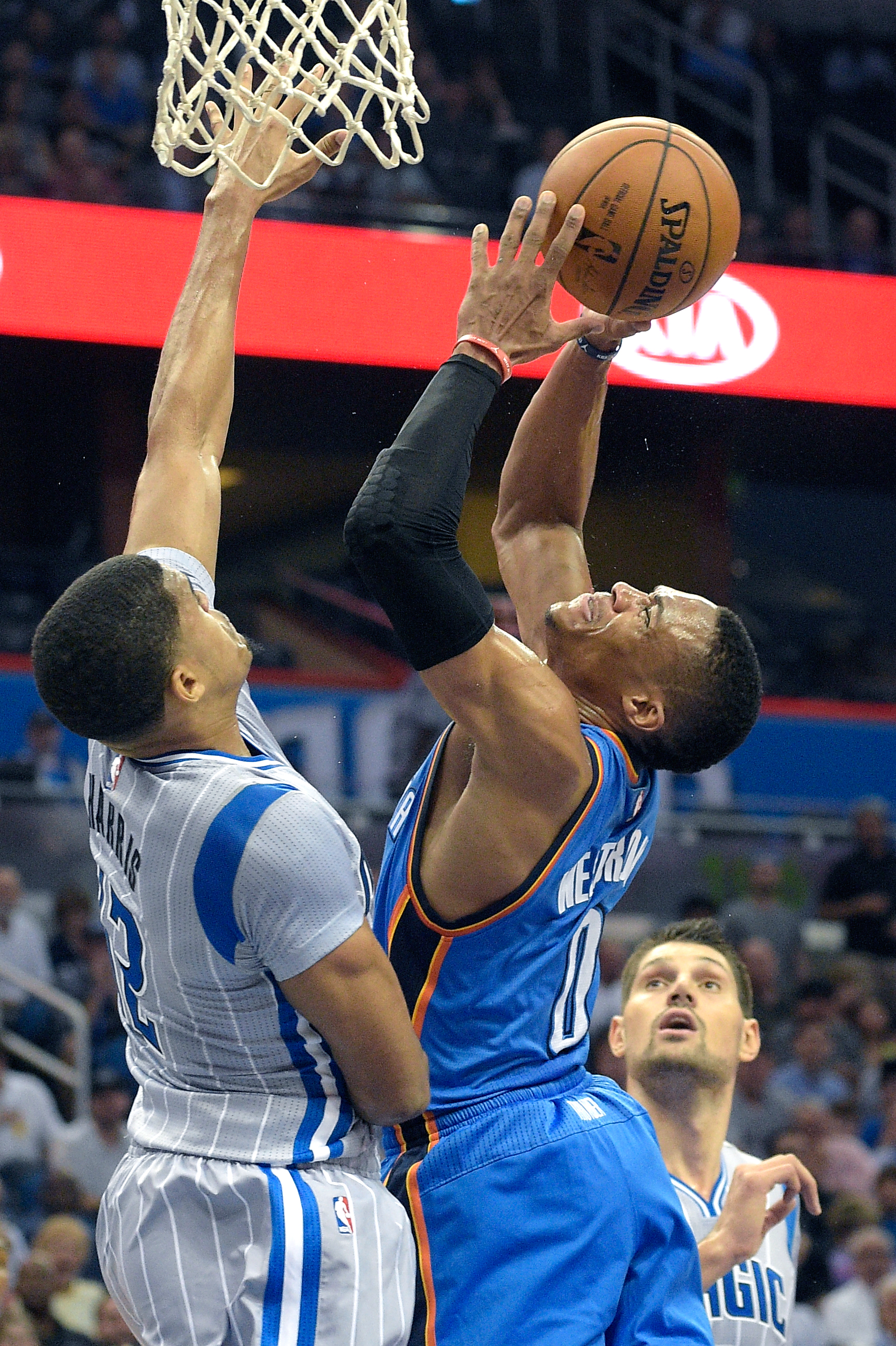 Oklahoma City Thunder guard Russell Westbrook (0) goes up to shoot between Orlando Magic forward Tobias Harris (12) and Nikola Vucevic, right, during the first half of an NBA basketball game in Orlando, Fla., Friday, Oct. 30, 2015. (AP Photo/Phelan M. Ebe