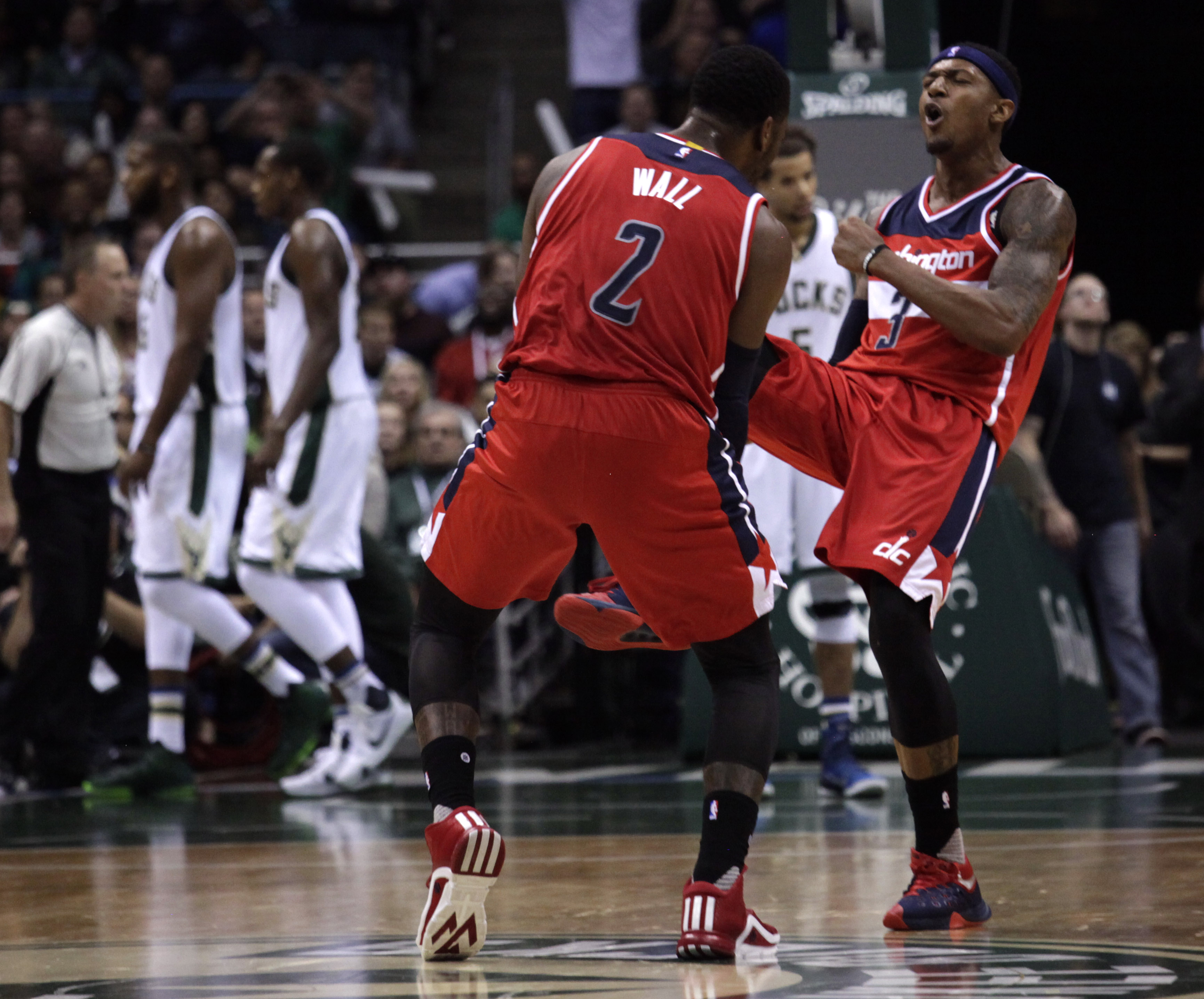 Washington Wizards guard Bradley Beal, right, reacts with teammate John Wall, left, after making a three-point basket against the Milwaukee Bucks during the second half of an NBA basketball game Friday, Oct. 30, 2015, in Milwaukee. The Wizards defeated th