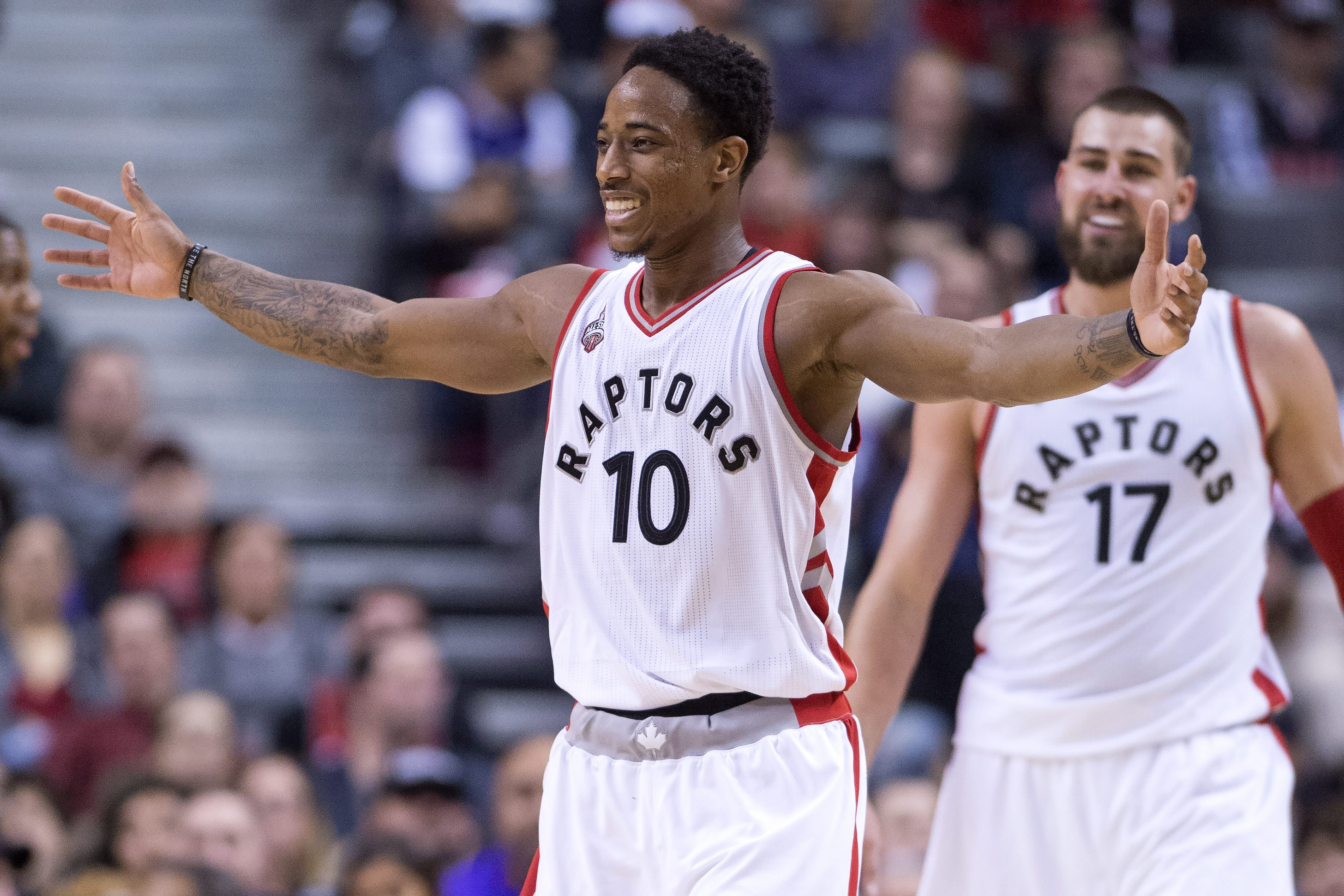 Toronto Raptors guard DeMar DeRozan and Jonas Valanciunas (17) celebrate a play during second half of an NBA basketball game against the Milwaukee Bucks in Toronto, Sunday, Nov. 1, 2015. (Frank Gunn/The Canadian Press via AP) MANDATORY CREDIT