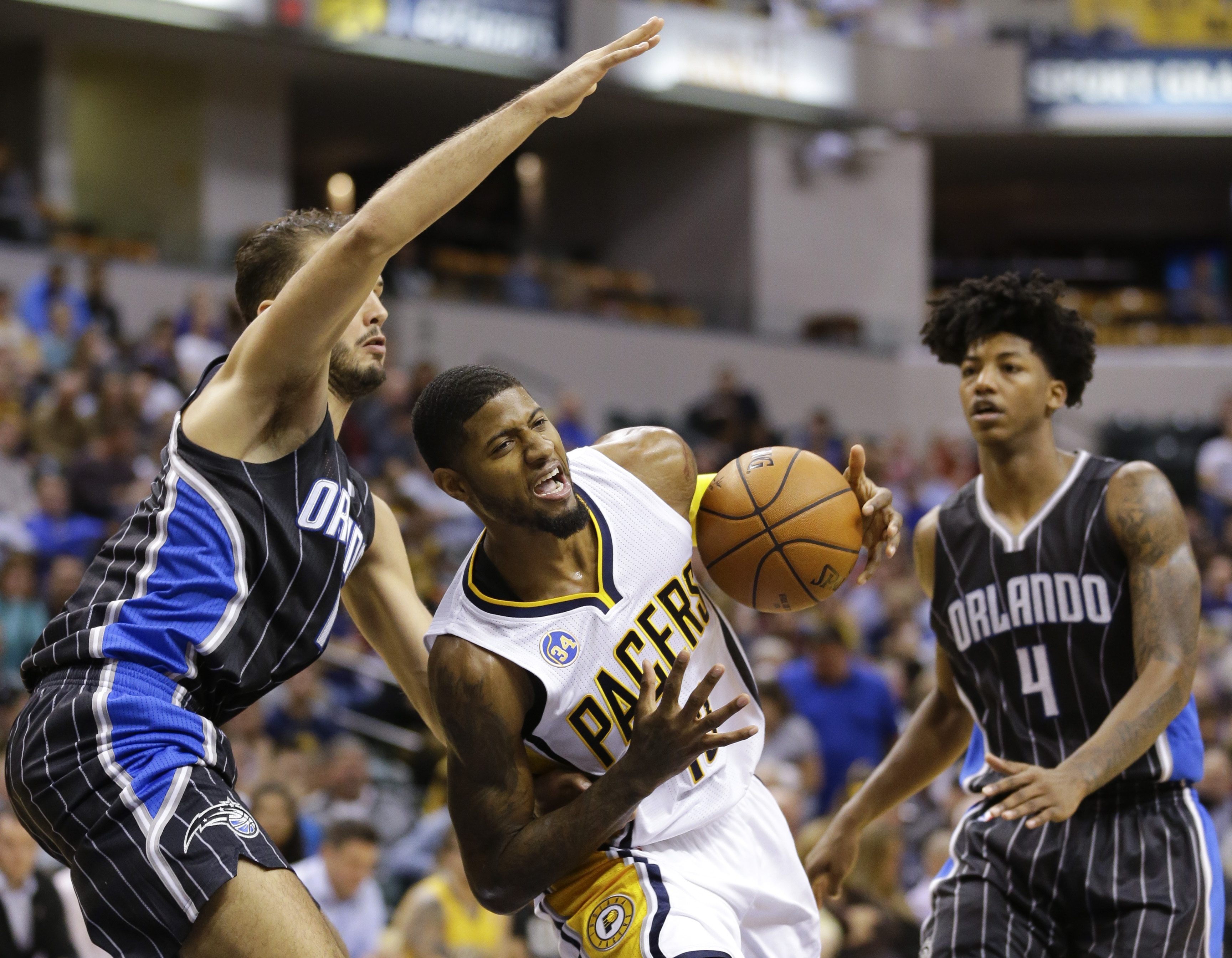 Indiana Pacers forward Paul George, center, is fouled as he cuts between Orlando Magic forward Evan Fournier, left, and guard Elfrid Payton (4) during the second half of an NBA basketball game in Indianapolis, Monday, Nov. 9, 2015. The Pacers won 97-84. (