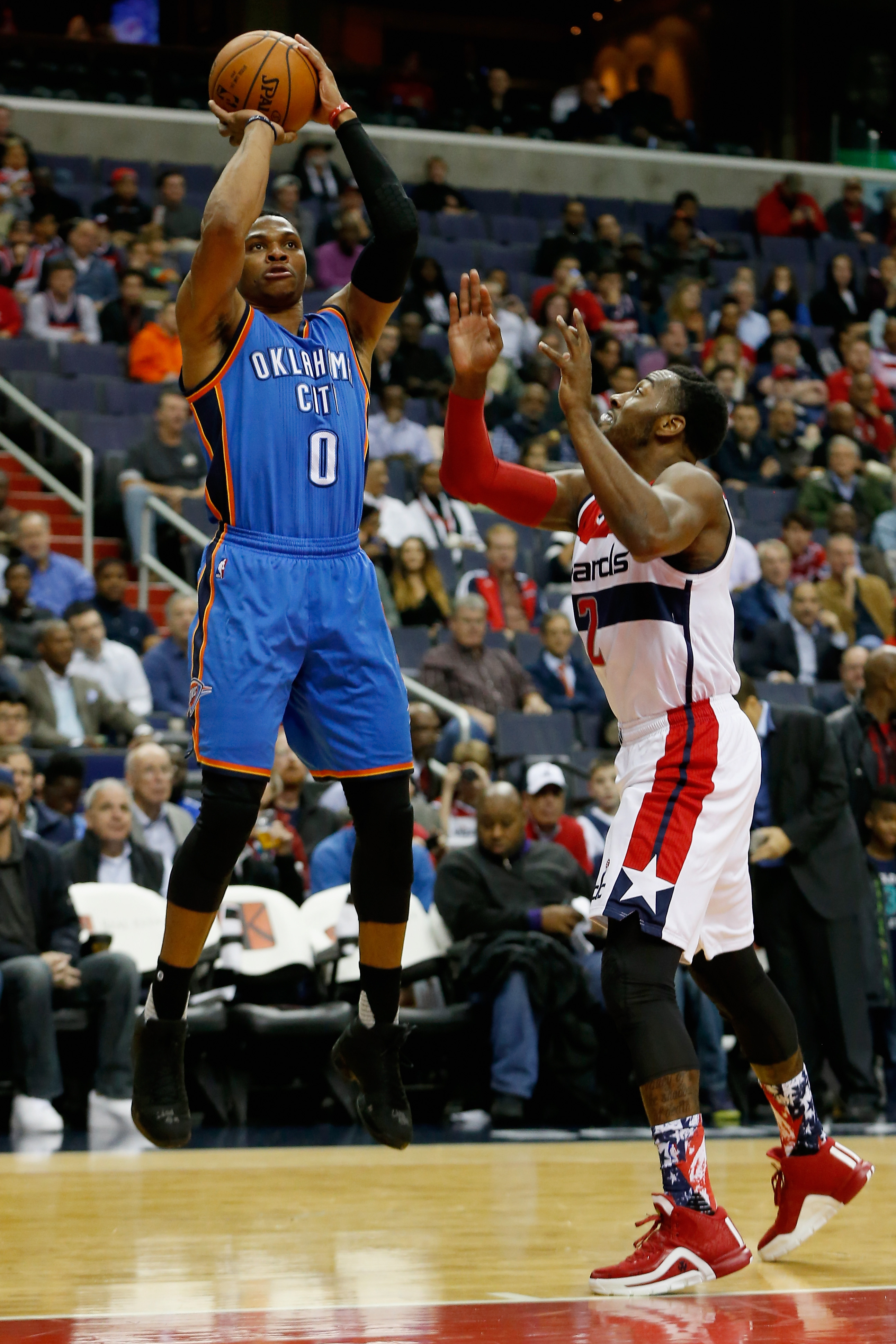 WASHINGTON, DC - NOVEMBER 10: Russell Westbrook #0 of the Oklahoma City Thunder puts a shot over the defense of John Wall #2 of the Washington Wizards in the first half at Verizon Center on November 10, 2015 in Washington, DC. (Photo by Rob Carr/Getty Ima