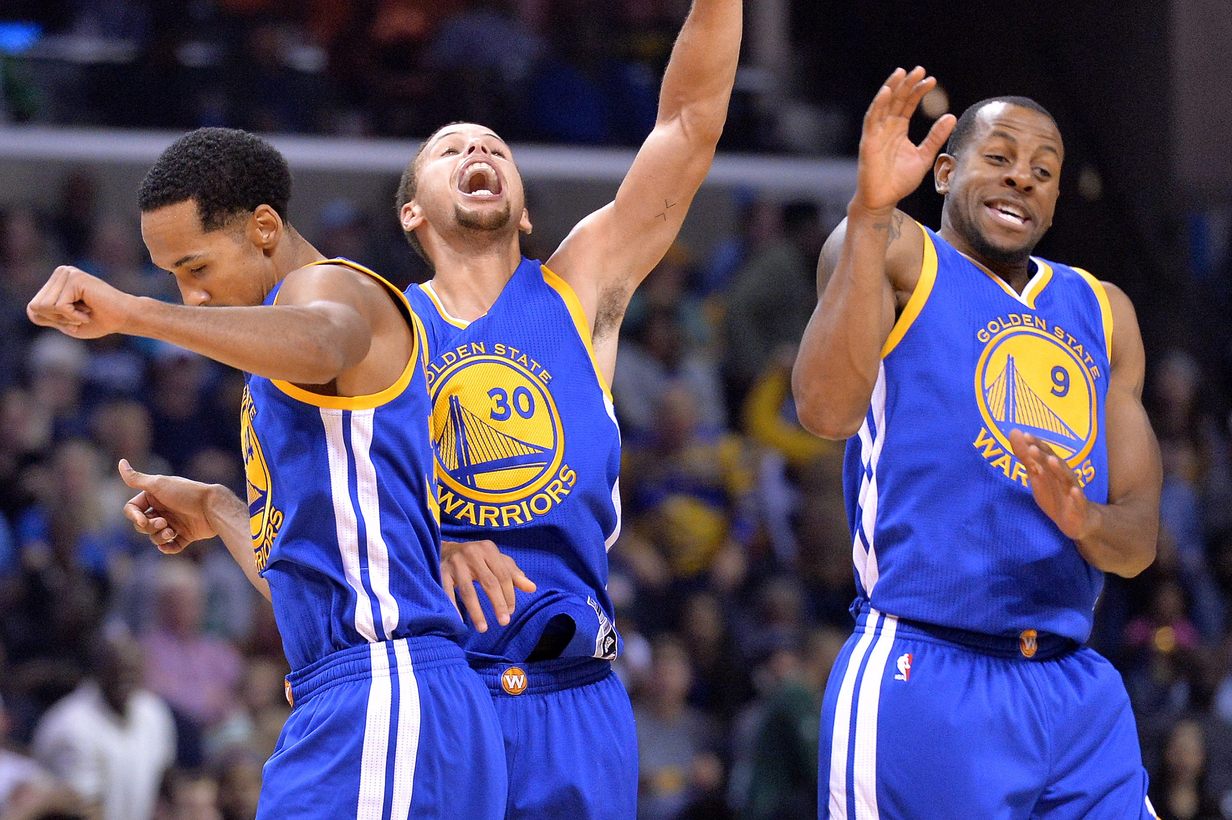 Golden State Warriors guards Shaun Livingston, left, Stephen Curry (30), and Andre Iguodala (9) celebrate after Curry's three-point score to beat the buzzer at the end of the third quarter during an NBA basketball game against the Memphis Grizzlies, Wedne
