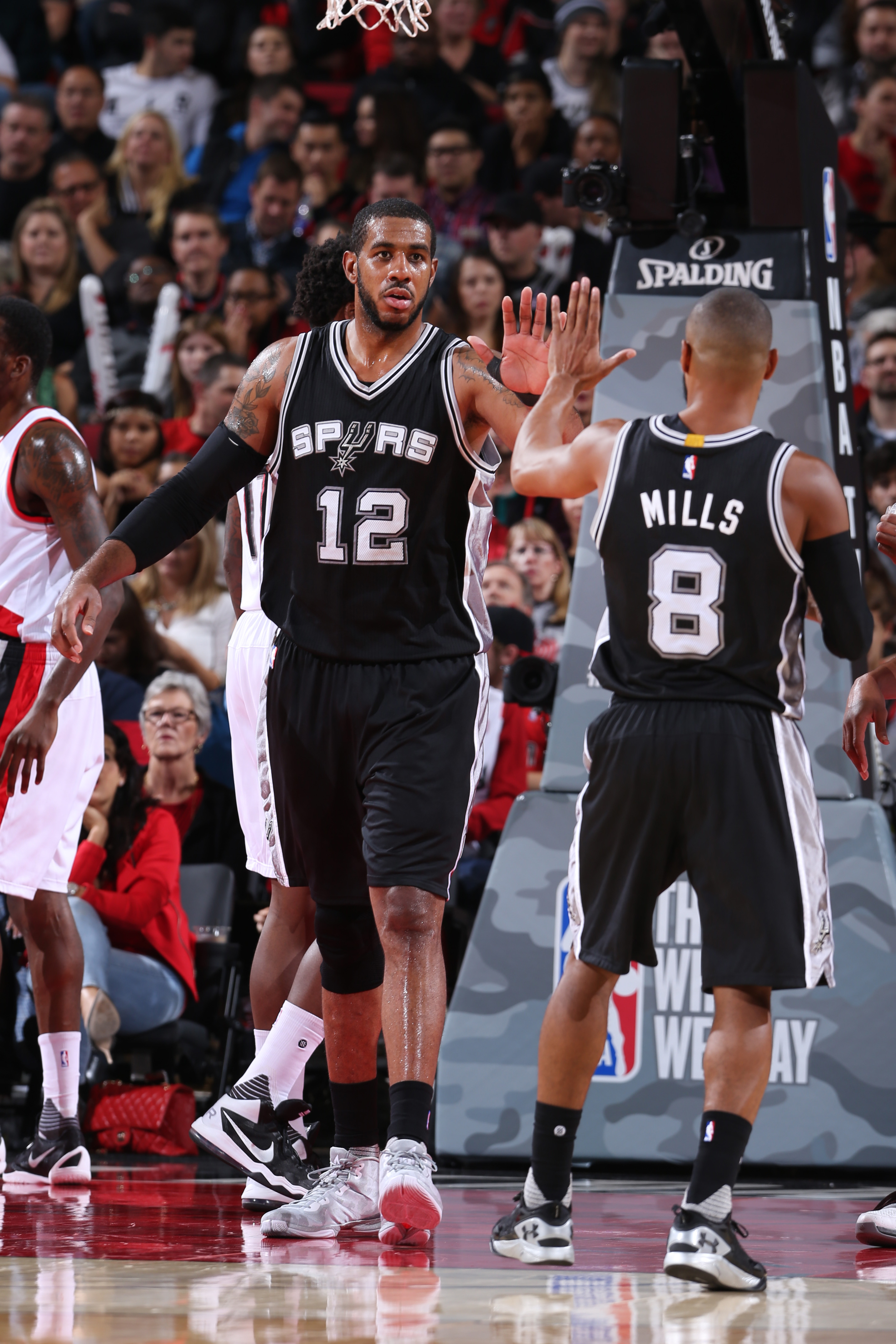 PORTLAND, OR - NOVEMBER 11: LaMarcus Aldridge #12 high fives Patty Mills #8 of the San Antonio Spurs during the game against the Portland Trail Blazers on November 11, 2015 at Moda Center in Portland, Oregon. (Photo by Sam Forencich/NBAE via Getty Images)