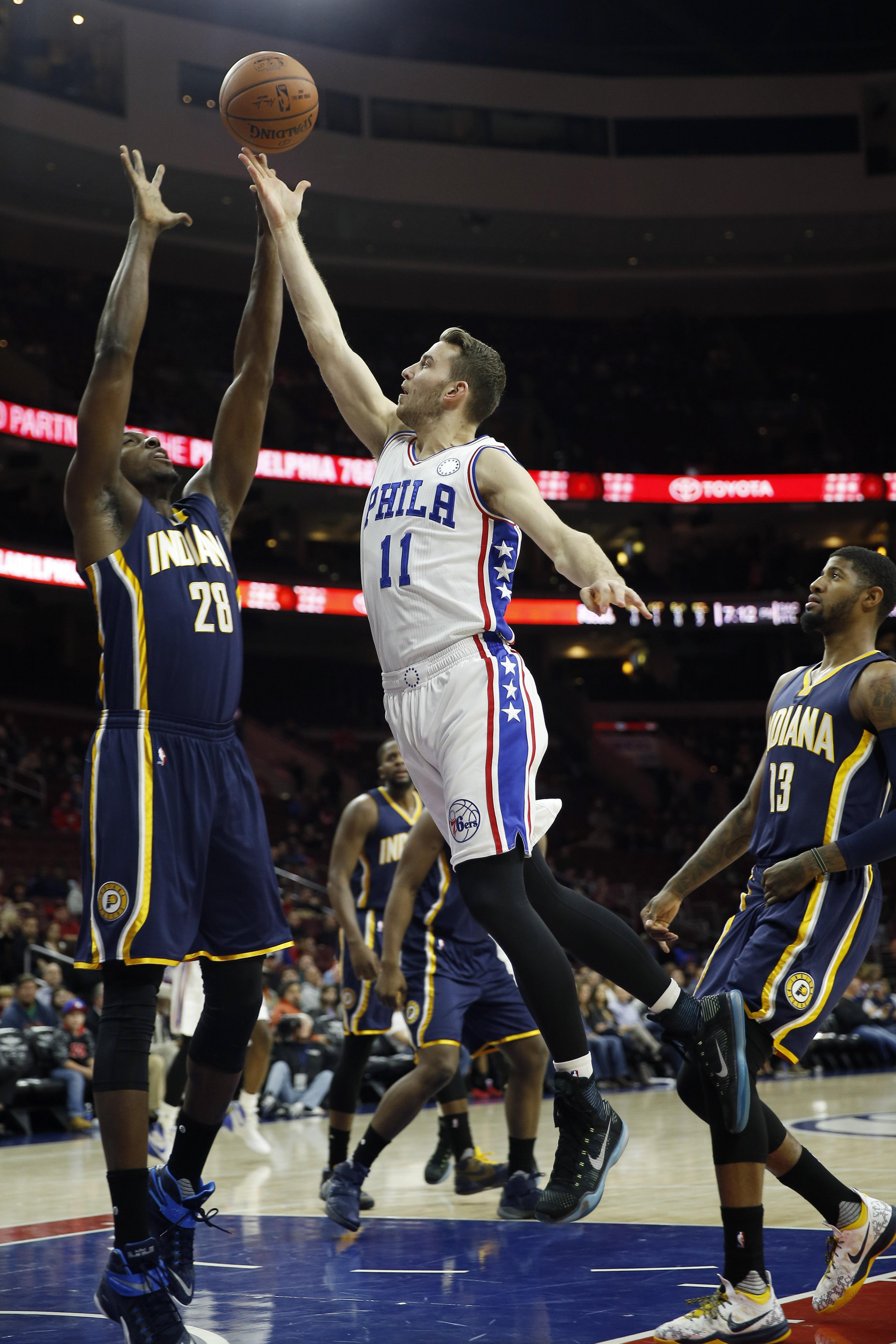 Philadelphia 76ers' Nik Stauskas (11) goes up for a shot between Indiana Pacers' Ian Mahinmi (28) and Paul George (13) during the first half of an NBA basketball game, Wednesday, Nov. 18, 2015, in Philadelphia. (AP Photo/Matt Slocum)