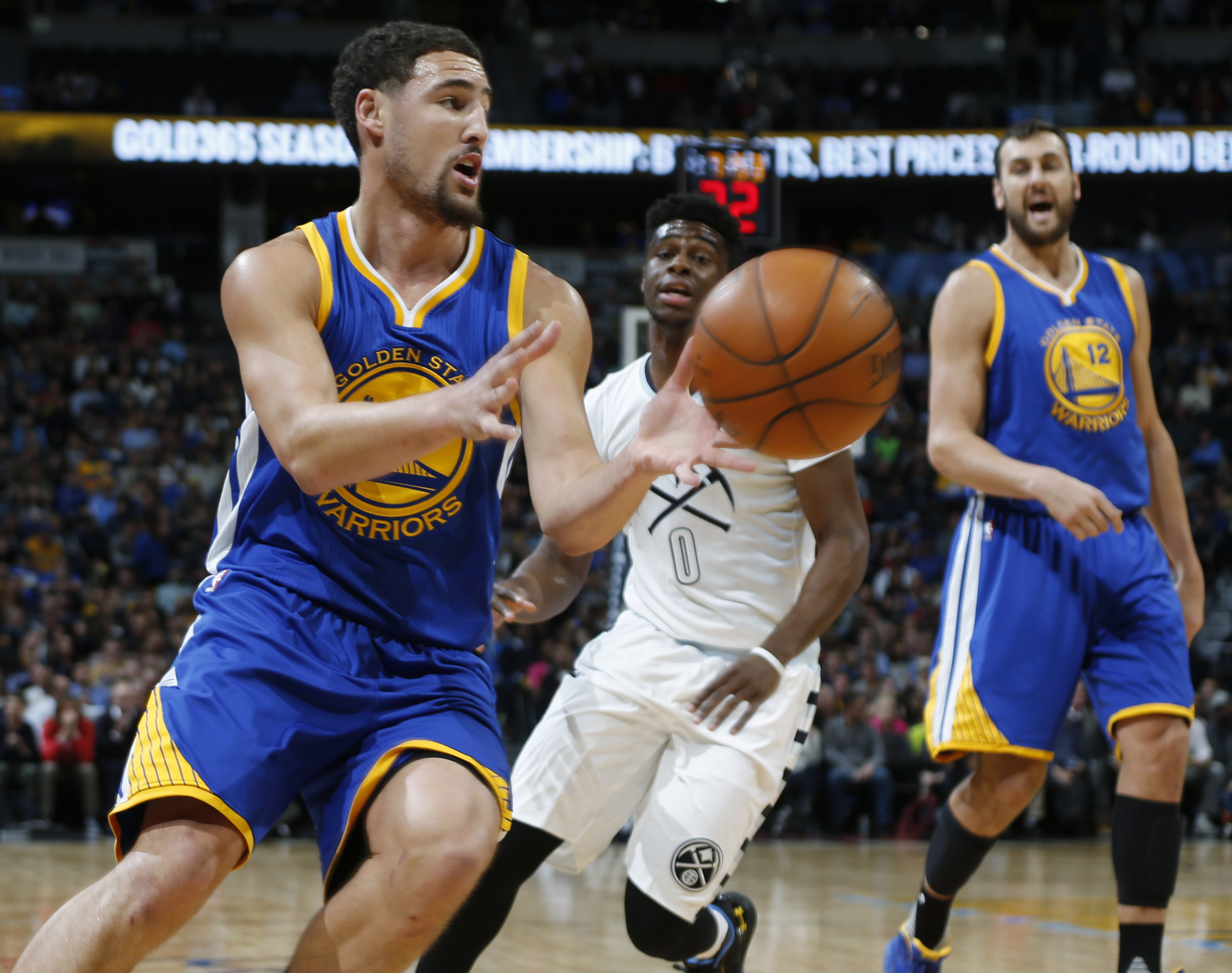 Golden State Warriors guard Klay Thompson, front, fields pass as Denver Nuggets guard Emmanuel Mudiay, center, defends during the first half of an NBA basketball game Sunday, Nov. 22, 2015, in Denver. (AP Photo/David Zalubowski)