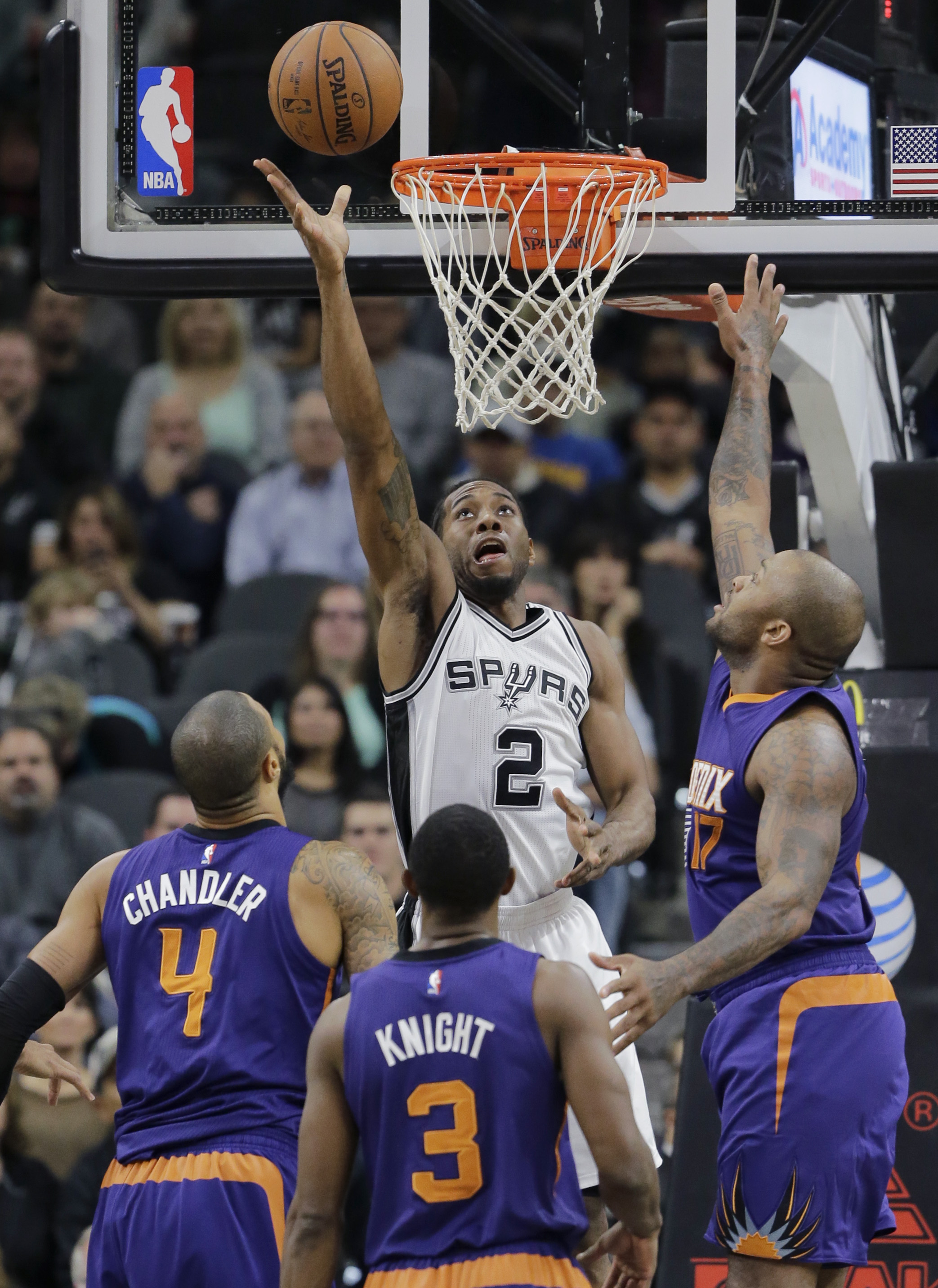 San Antonio Spurs' Kawhi Leonard (2) scores over Phoenix Suns defenders Tyson Chandler (4), Brandon Knight (3) and P.J. Tucker (17) during the first half of an NBA basketball game, Monday, Nov. 23, 2015, in San Antonio. (AP Photo/Eric Gay)