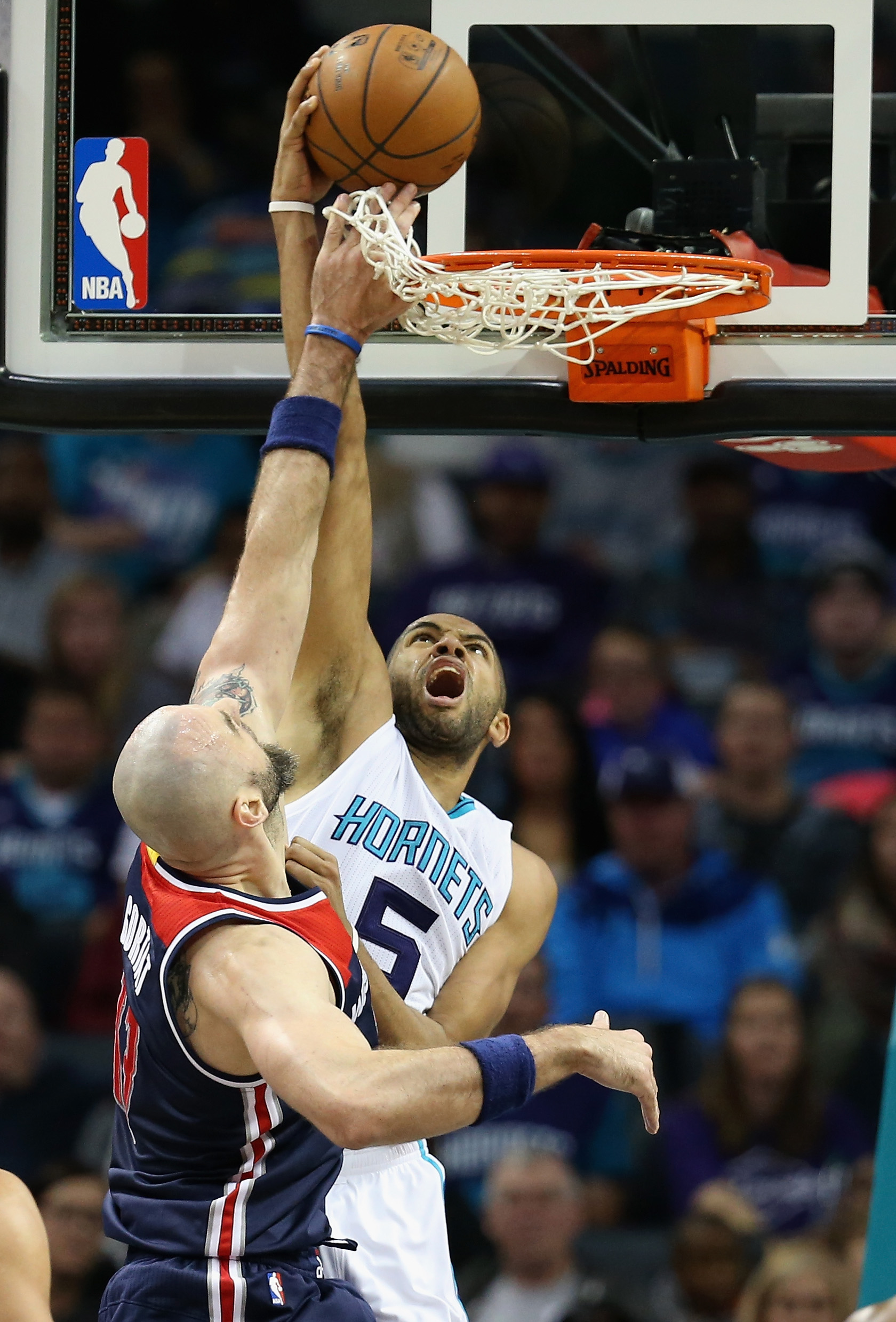 CHARLOTTE, NC - NOVEMBER 25:  Nicolas Batum #5 of the Charlotte Hornets drives to the basket against Marcin Gortat #13 of the Washington Wizards during their game at Time Warner Cable Arena on November 25, 2015 in Charlotte, North Carolina.  NBA - (Photo