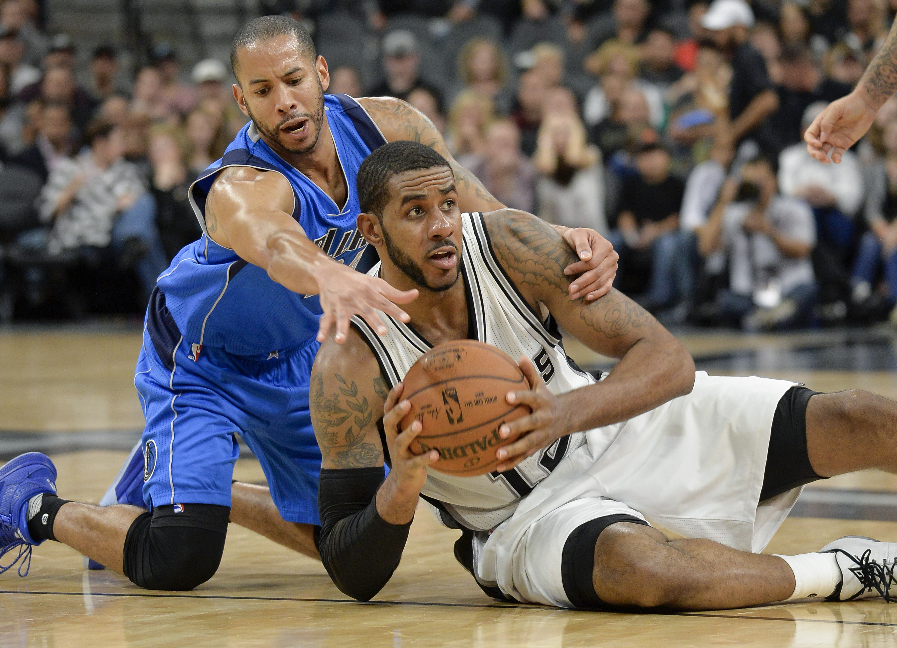 San Antonio Spurs forward LaMarcus Aldridge, right, tangles with Dallas Mavericks guard Devin Harris during the second half of an NBA basketball game, Wednesday, Nov. 25, 2015, in San Antonio. San Antonio won 88-83. (AP Photo/Darren Abate)