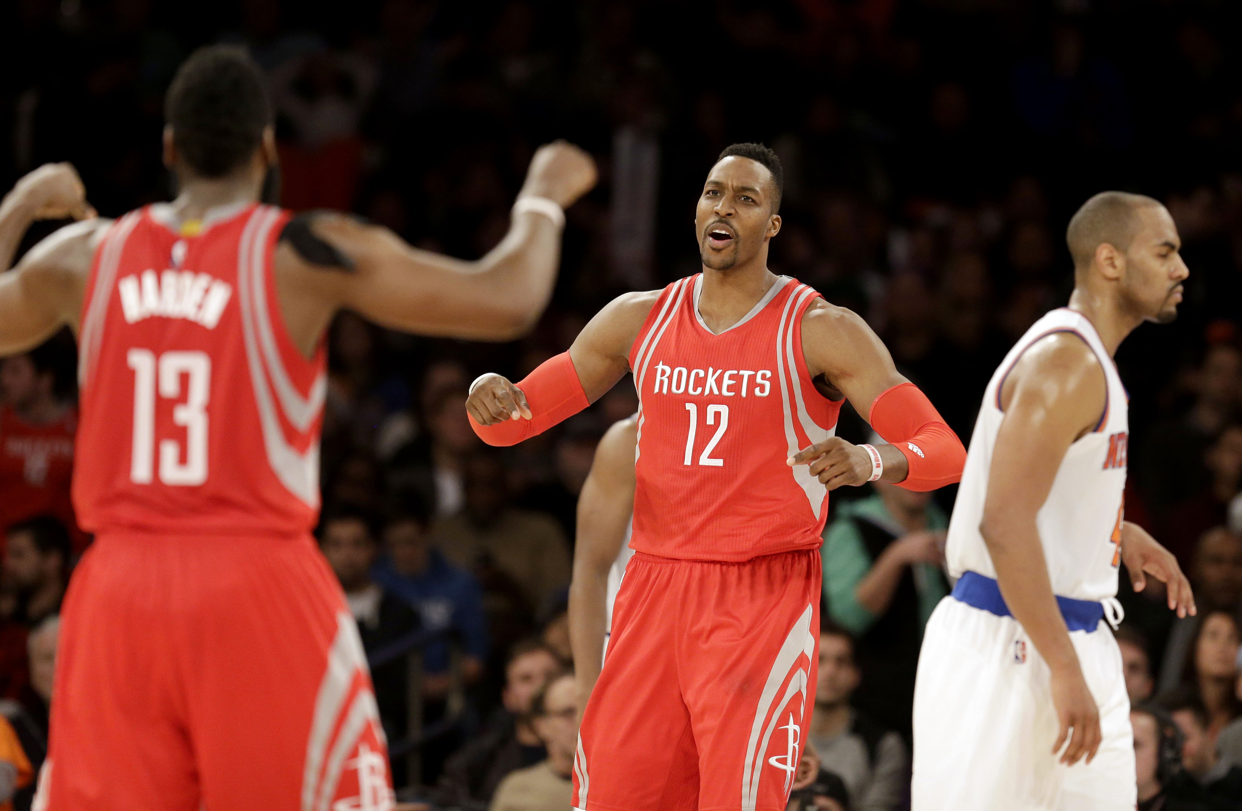 Houston Rockets' Dwight Howard, center, celebrates with James Harden, left, while New York Knicks' Arron Afflalo walks away during the overtime period of the NBA basketball game against the New York Knicks, Sunday, Nov. 29, 2015, in New York. (AP Photo/Se